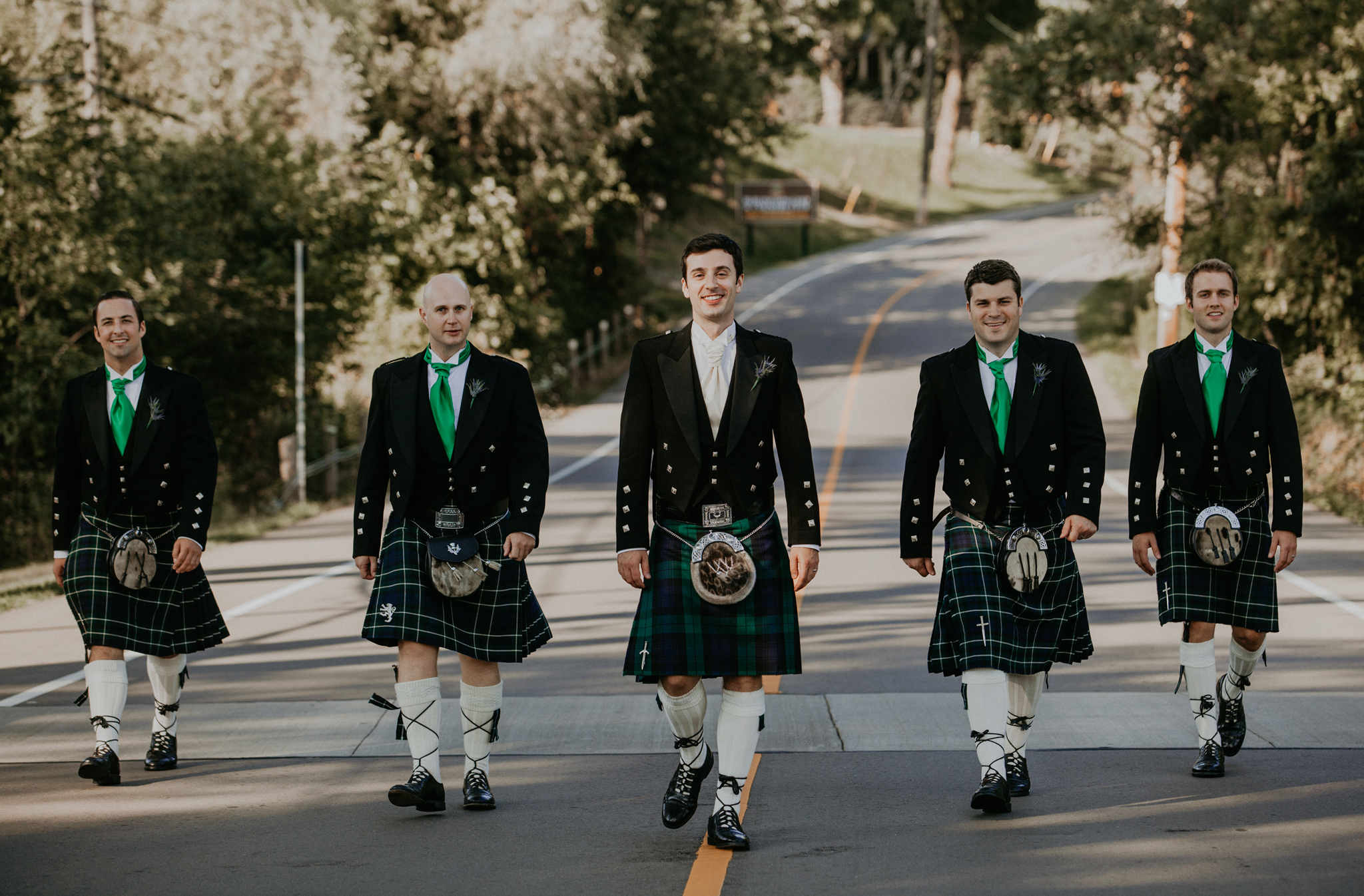 Groom and groomsmen in kilts walking down street