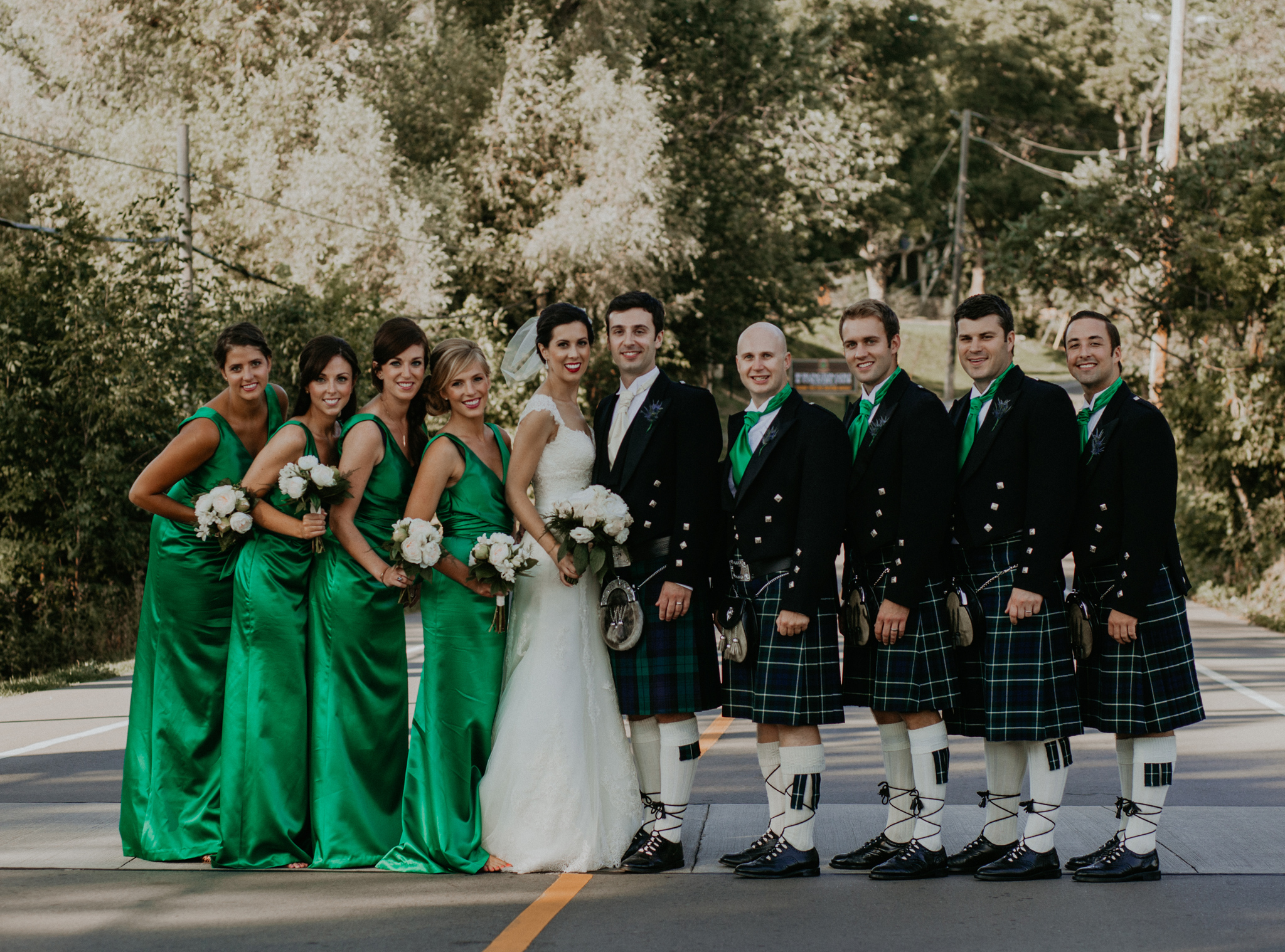 portrait of wedding party in kilts and green dresses posing in street