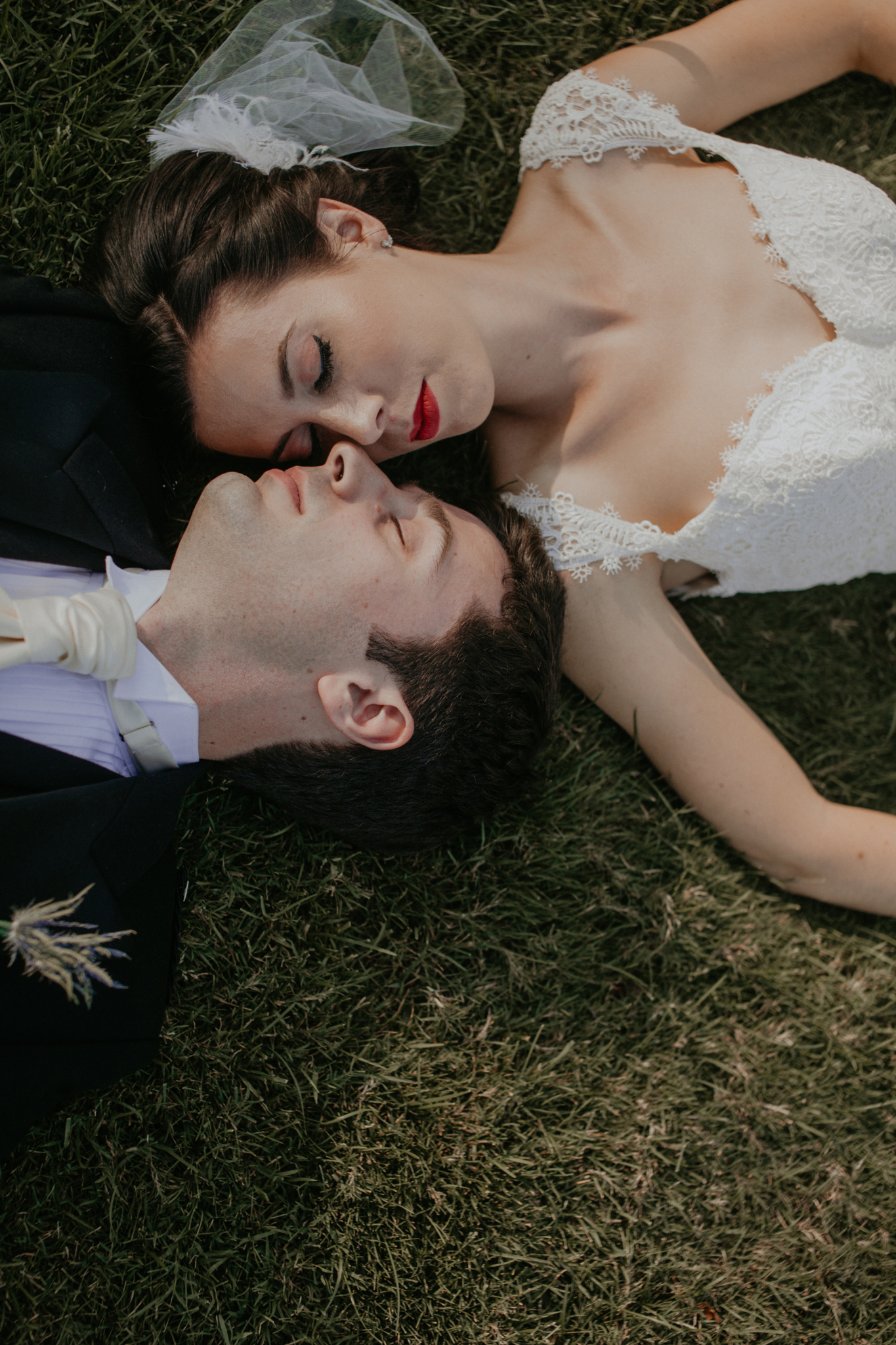 Bride and groom laying in grass romantic wedding photo