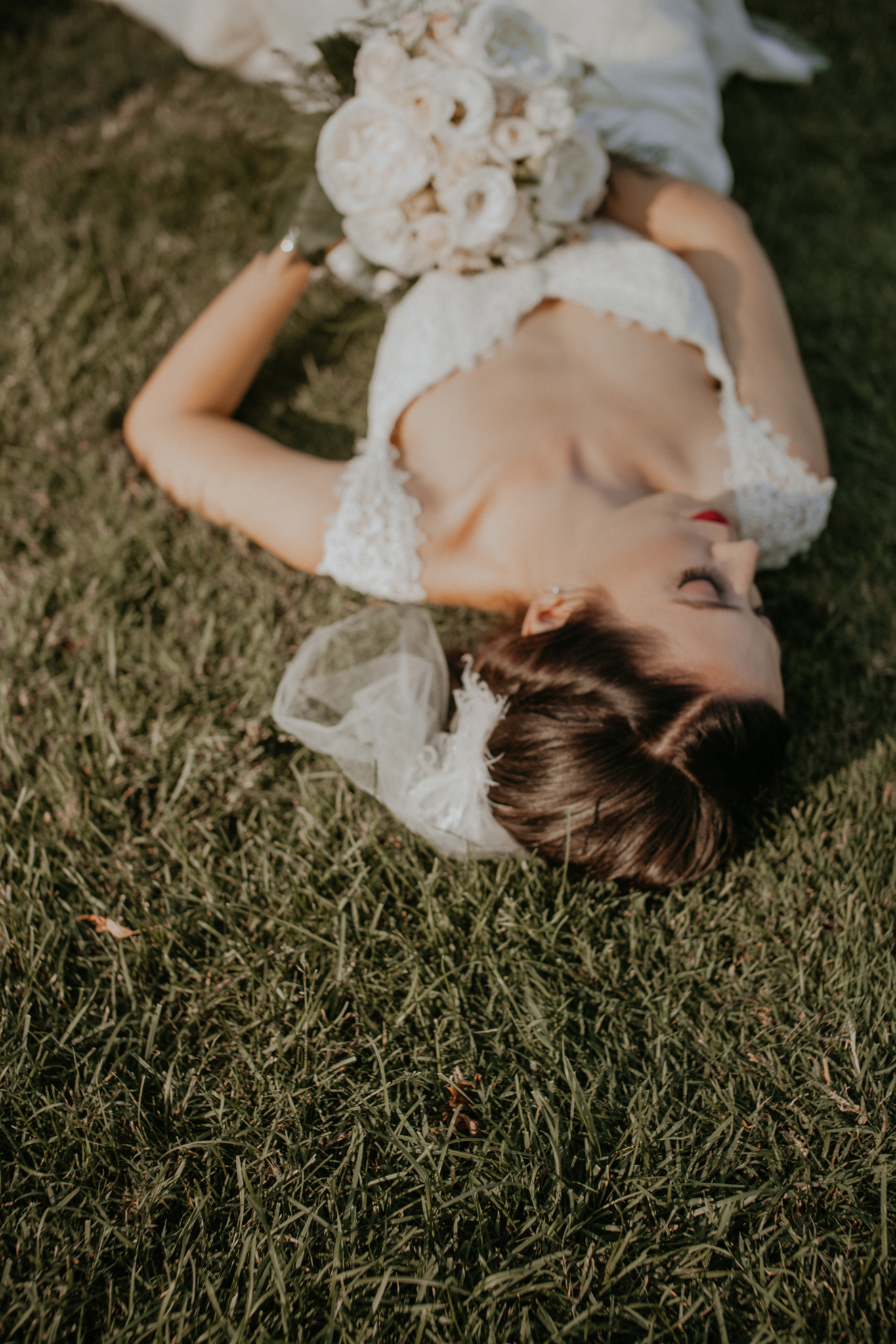 Bride lays down in grass holding bouquet