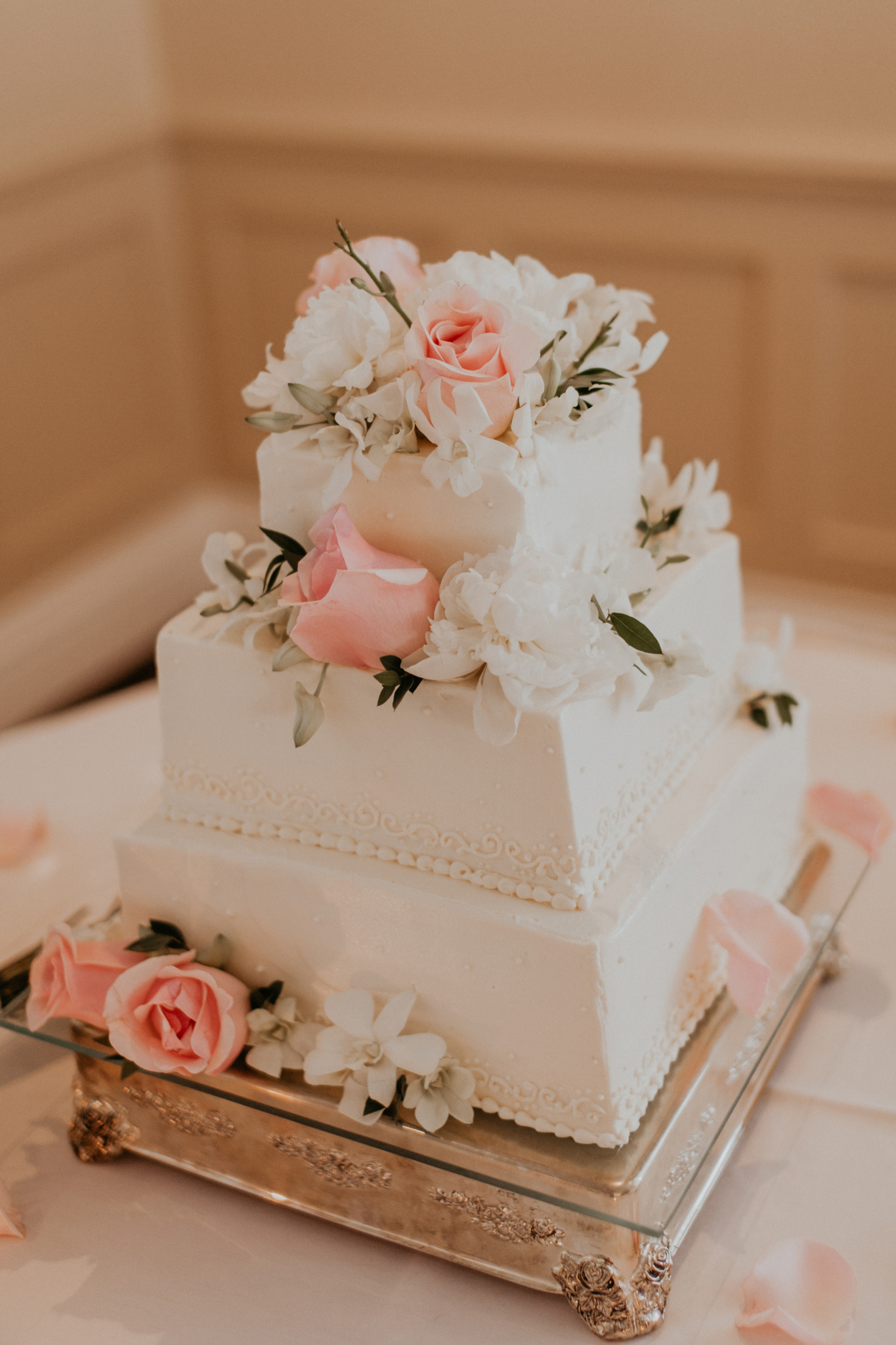Wedding cake on table with pink roses