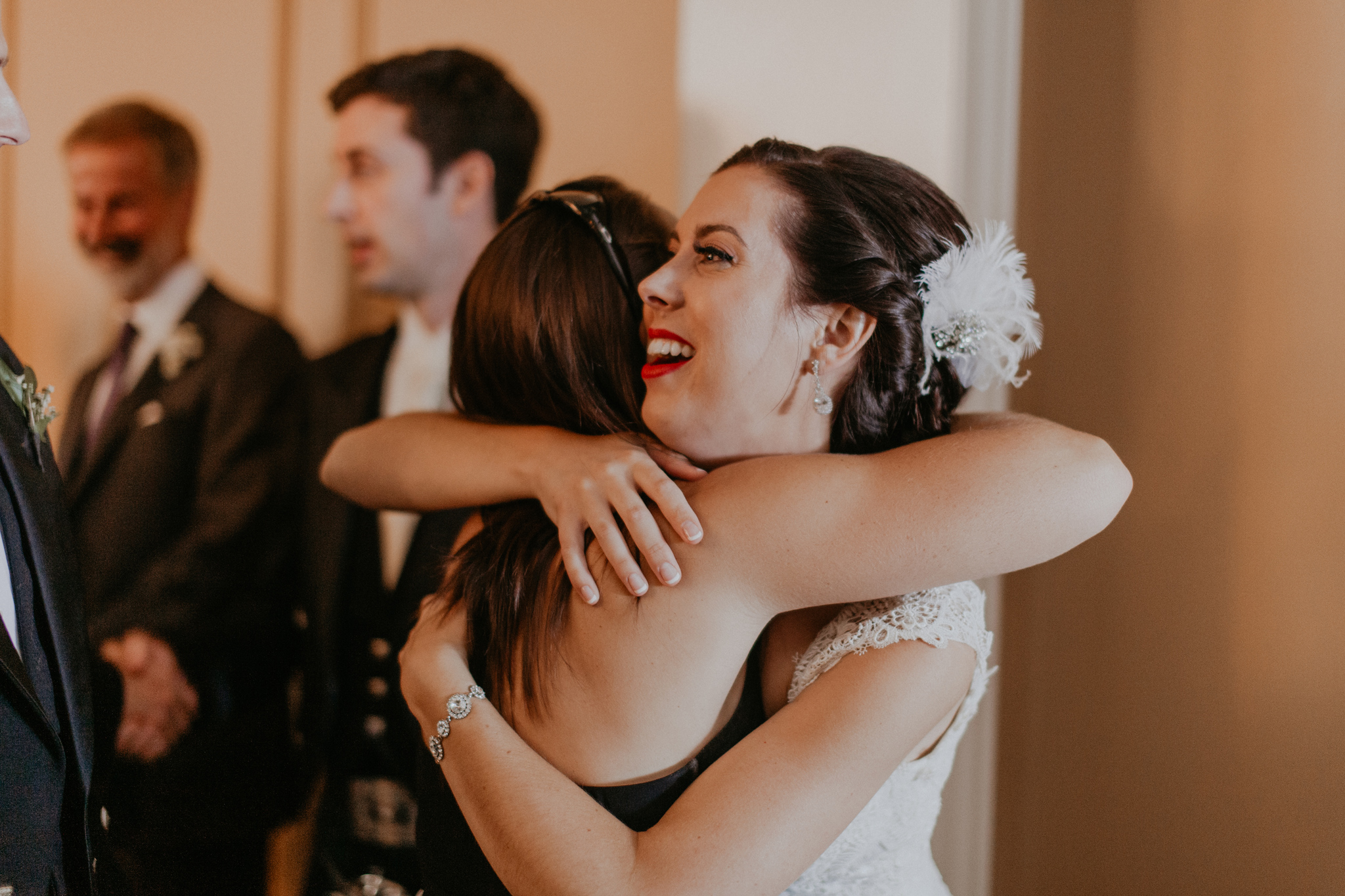 Bride hugs guest in candid documentary wedding photo