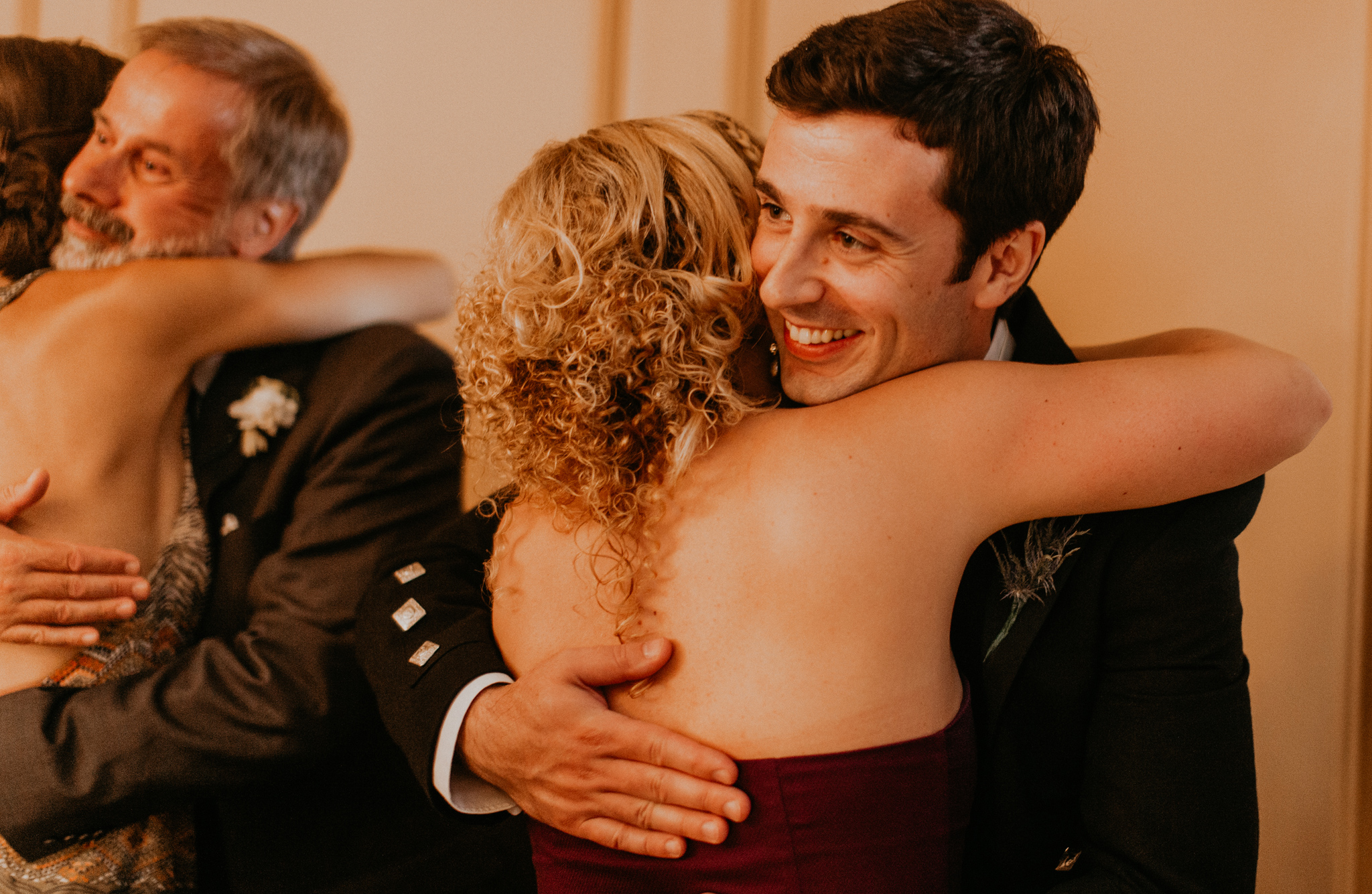 Groom hugs guest at wedding in candid photo