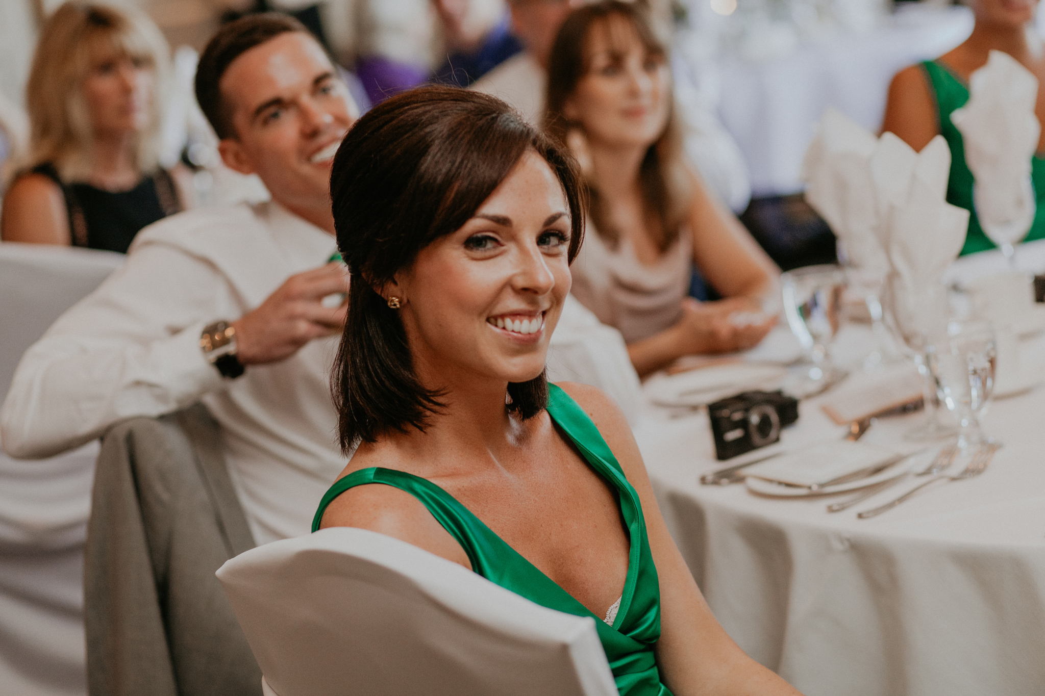 Bridesmaid in green dress smiles during reception documentary wedding photo