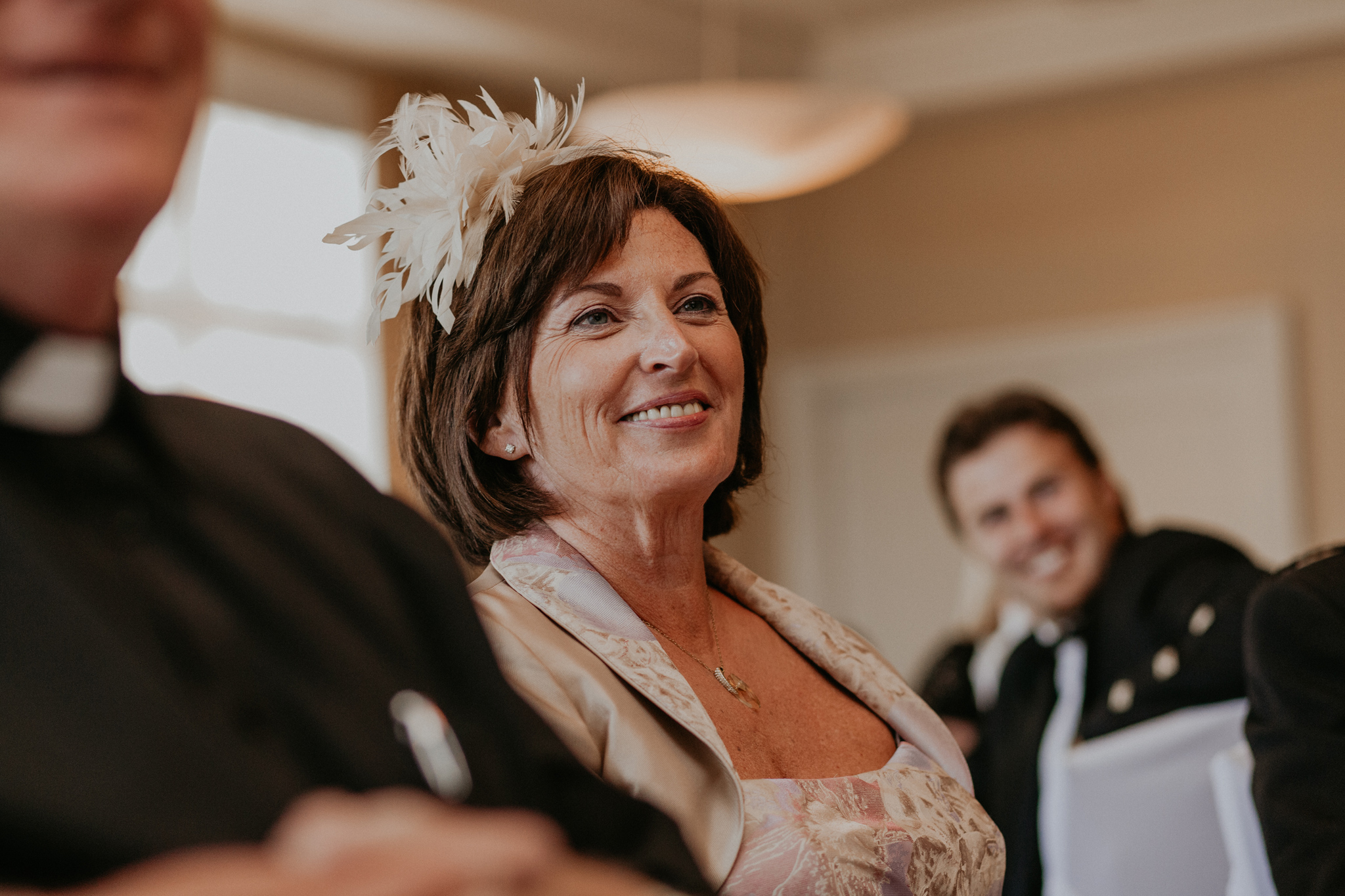 Mother of groom smiles during speeches at reception