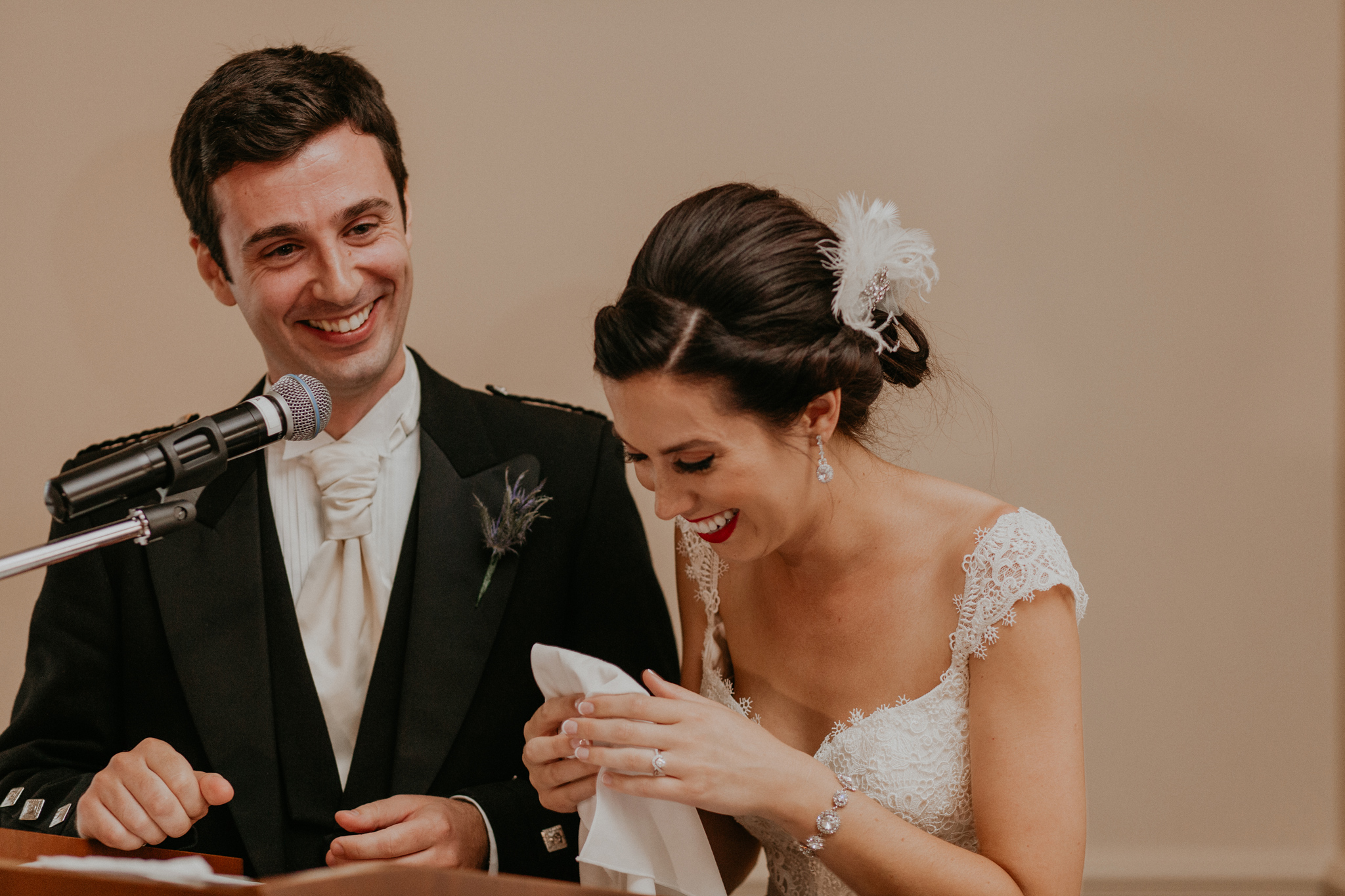 Bride and groom laugh in candid photo during speech