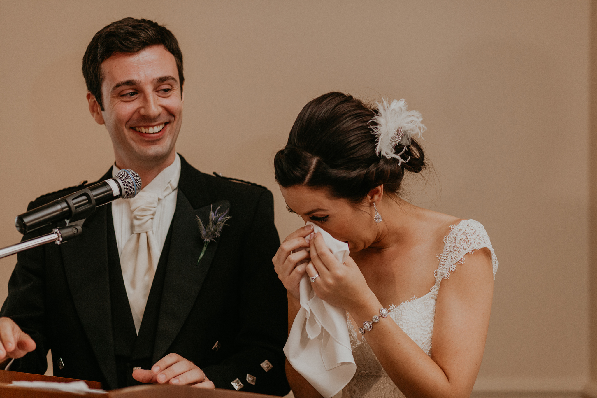 Bride wipes tears from eyes during wedding speech