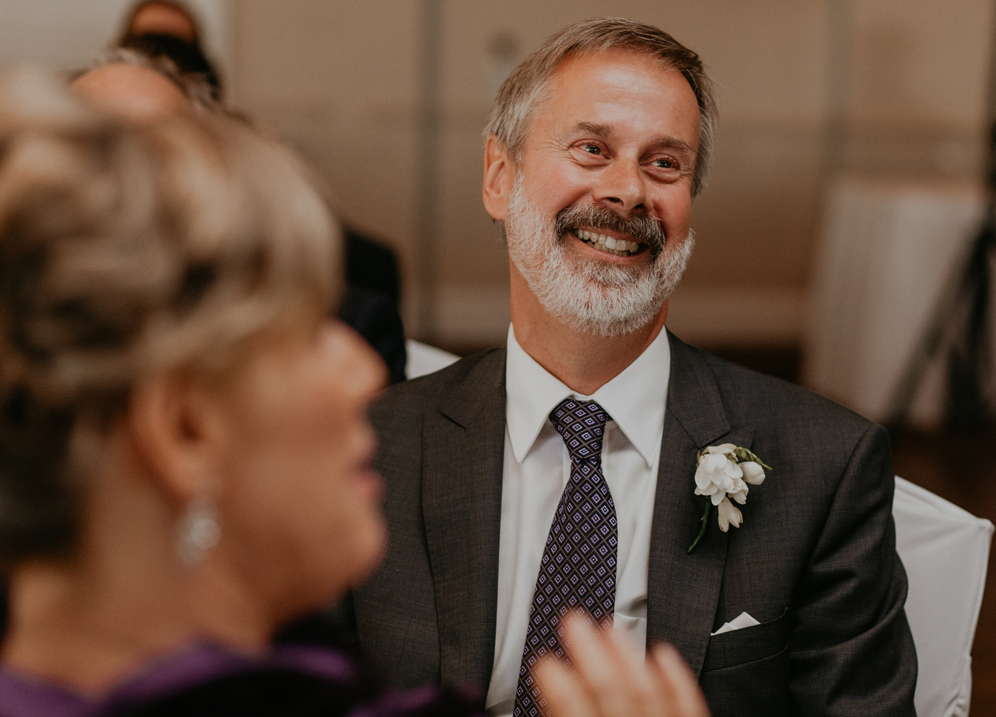 Father laughs during wedding reception for bride and groom in candid photo
