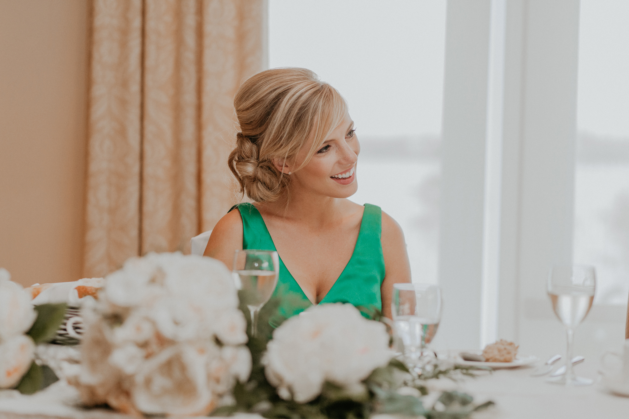 Maid of honor smiles at head table in wedding reception