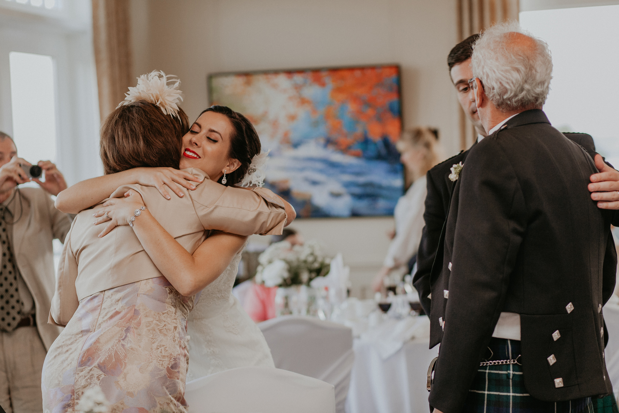 Couple embraces parents after speeches at wedding reception