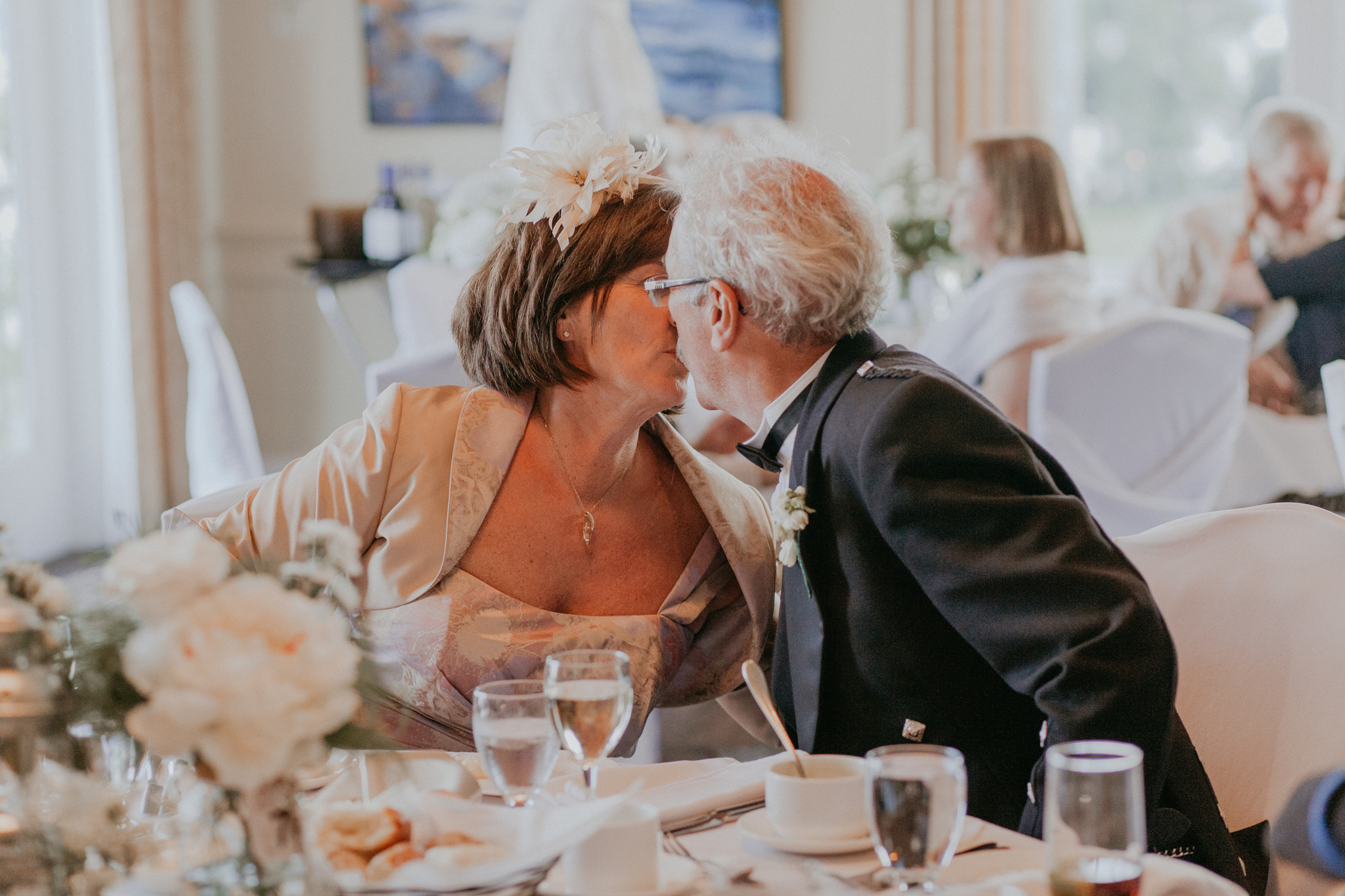 Candid photo of kiss between mother and father of the groom during wedding reception