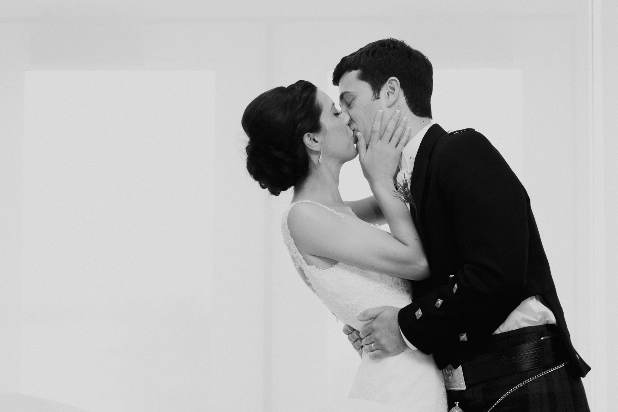 Black and white candid photo of bride and groom kissing romantic photograph