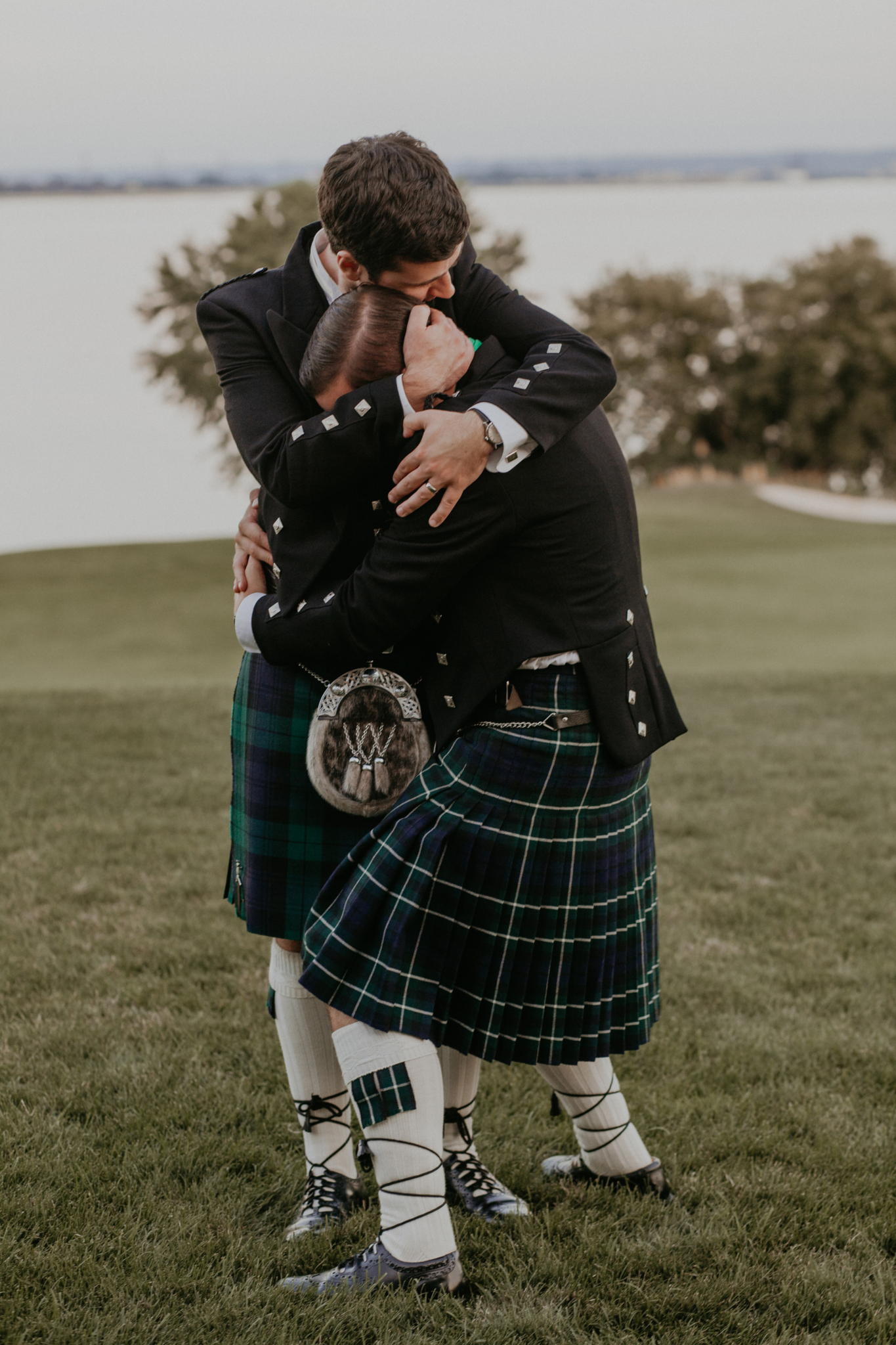 Documentary wedding photo candid of groom with best man hugging
