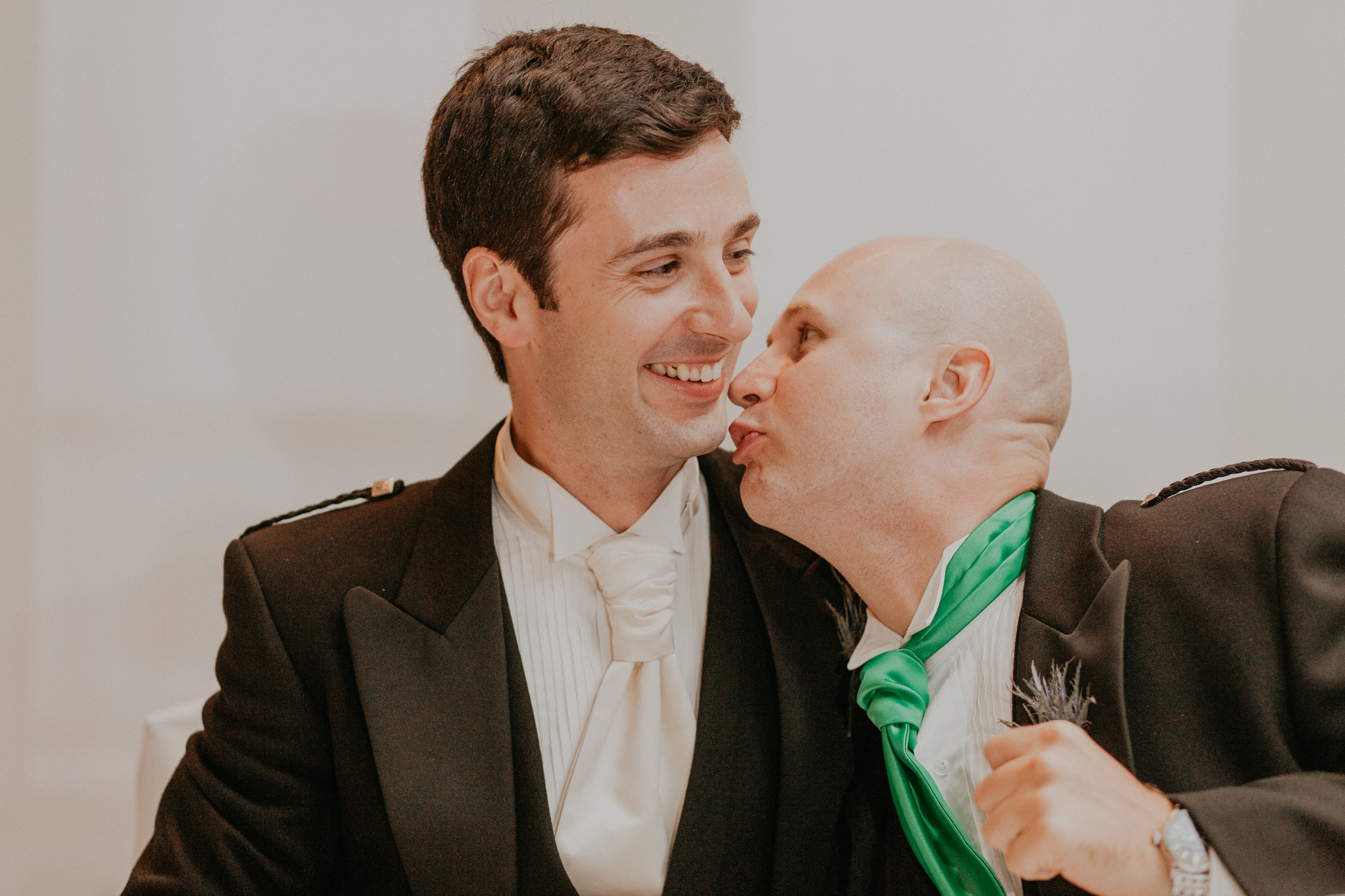 Groomsmen jokes and kisses groom during wedding reception