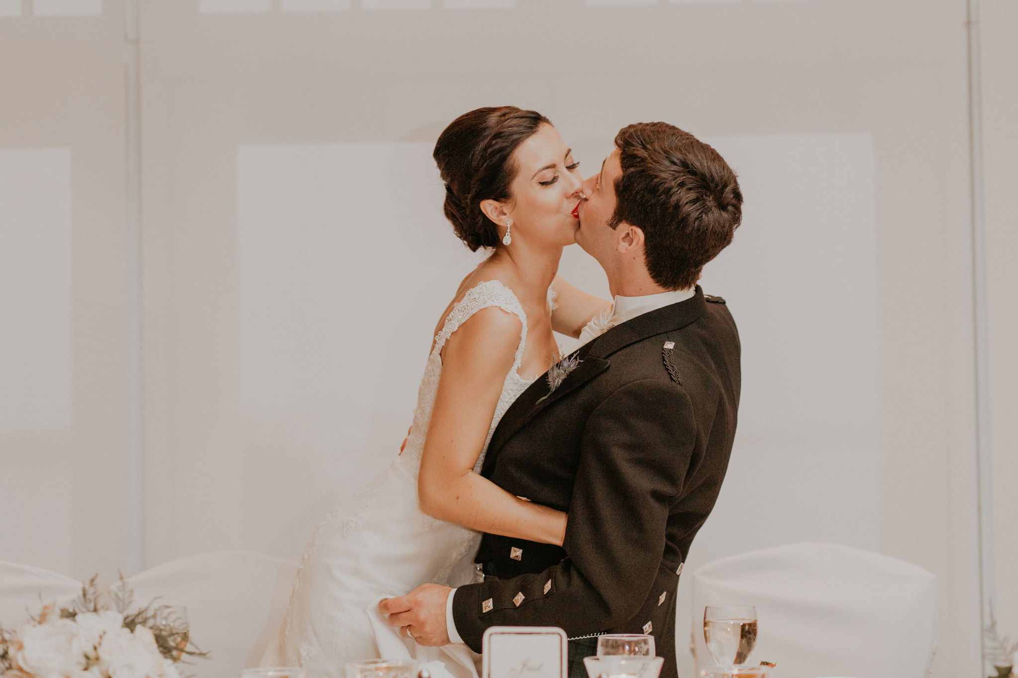 Bride and groom kiss during wedding reception