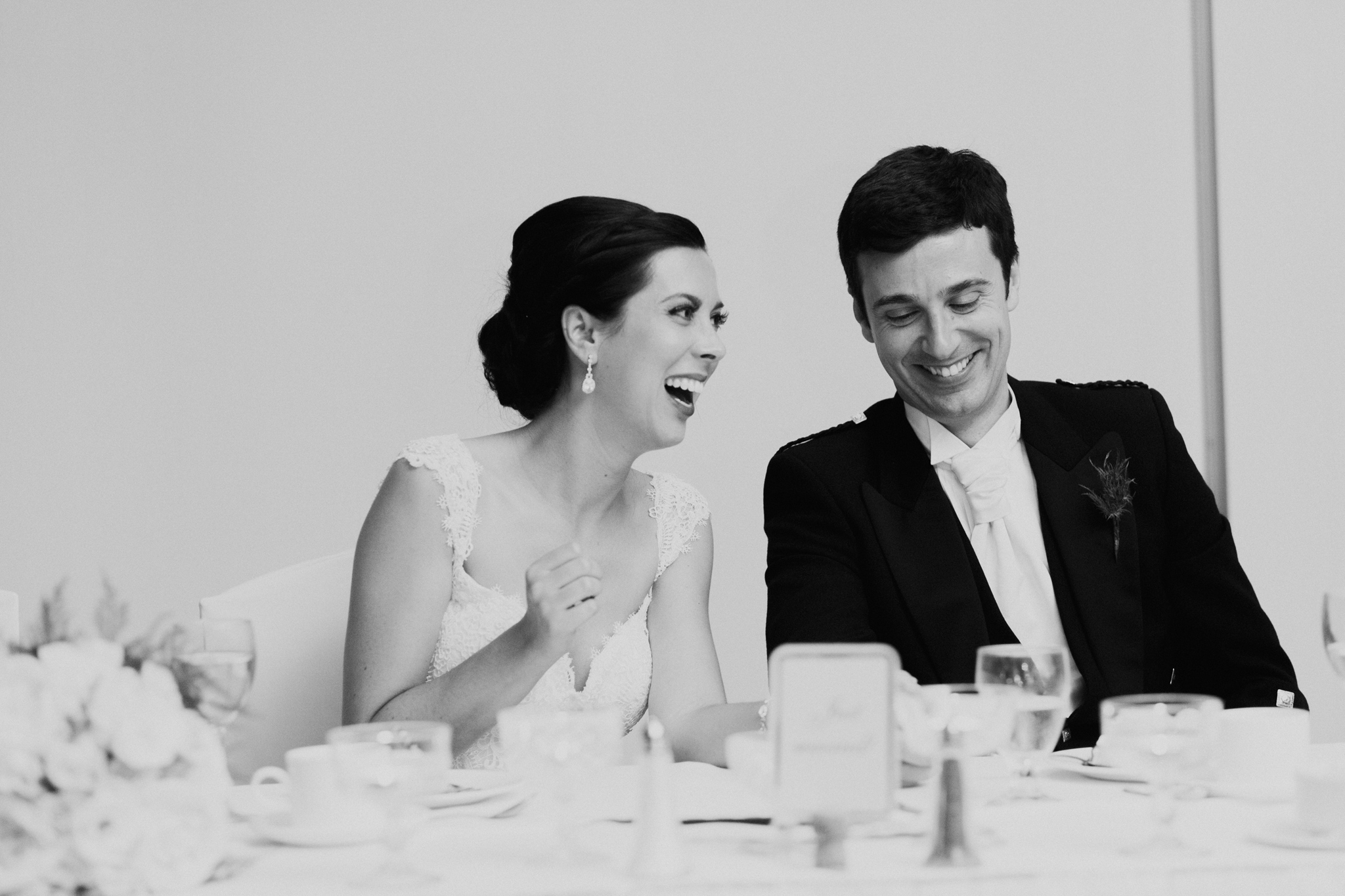 Black and white documentary photo of Bride and Groom laughing during speeches