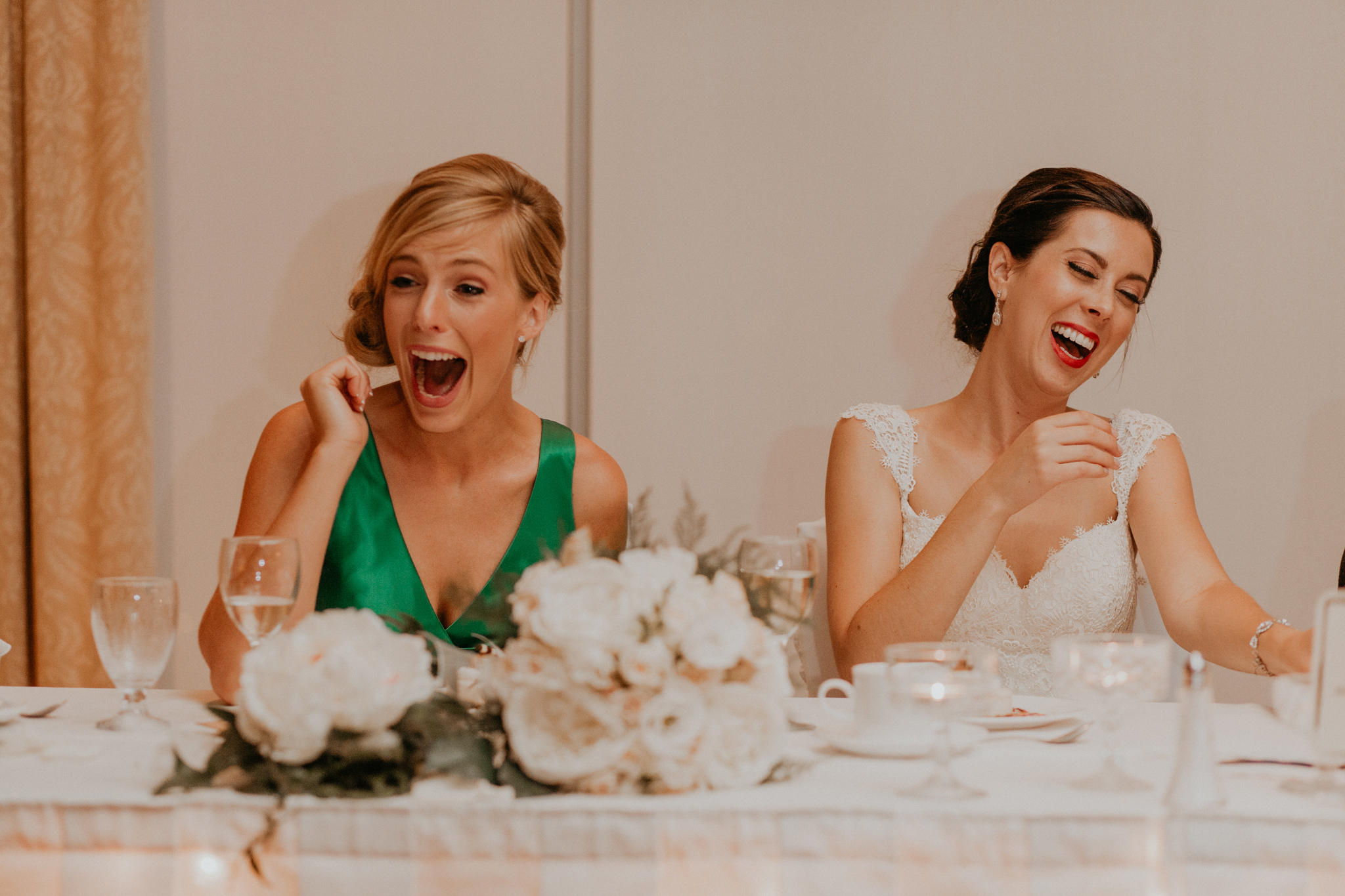 Candid of bride and bridesmaid laughing during wedding reception speeches