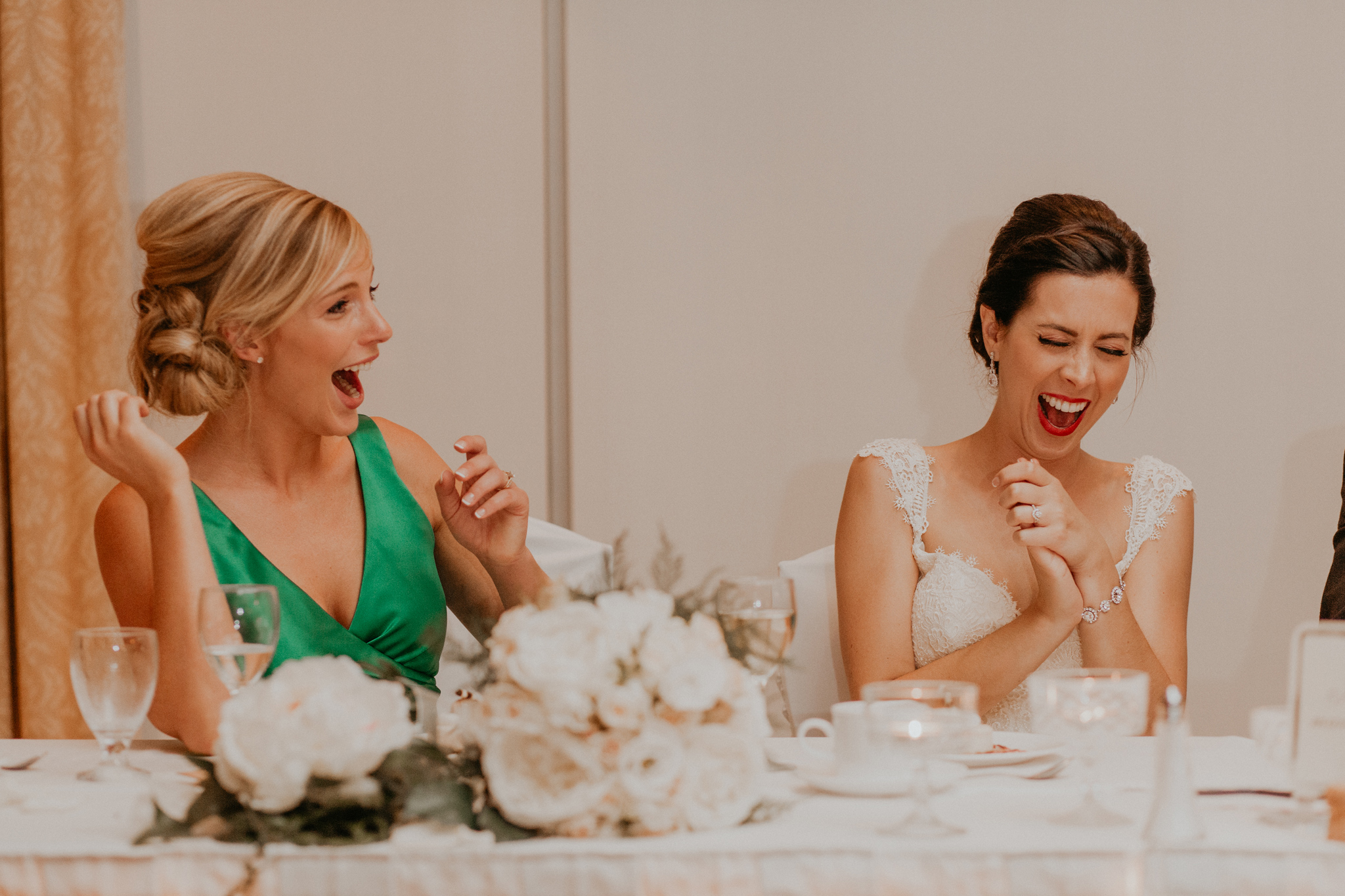 Bride and bridesmaid laugh during wedding reception speeches