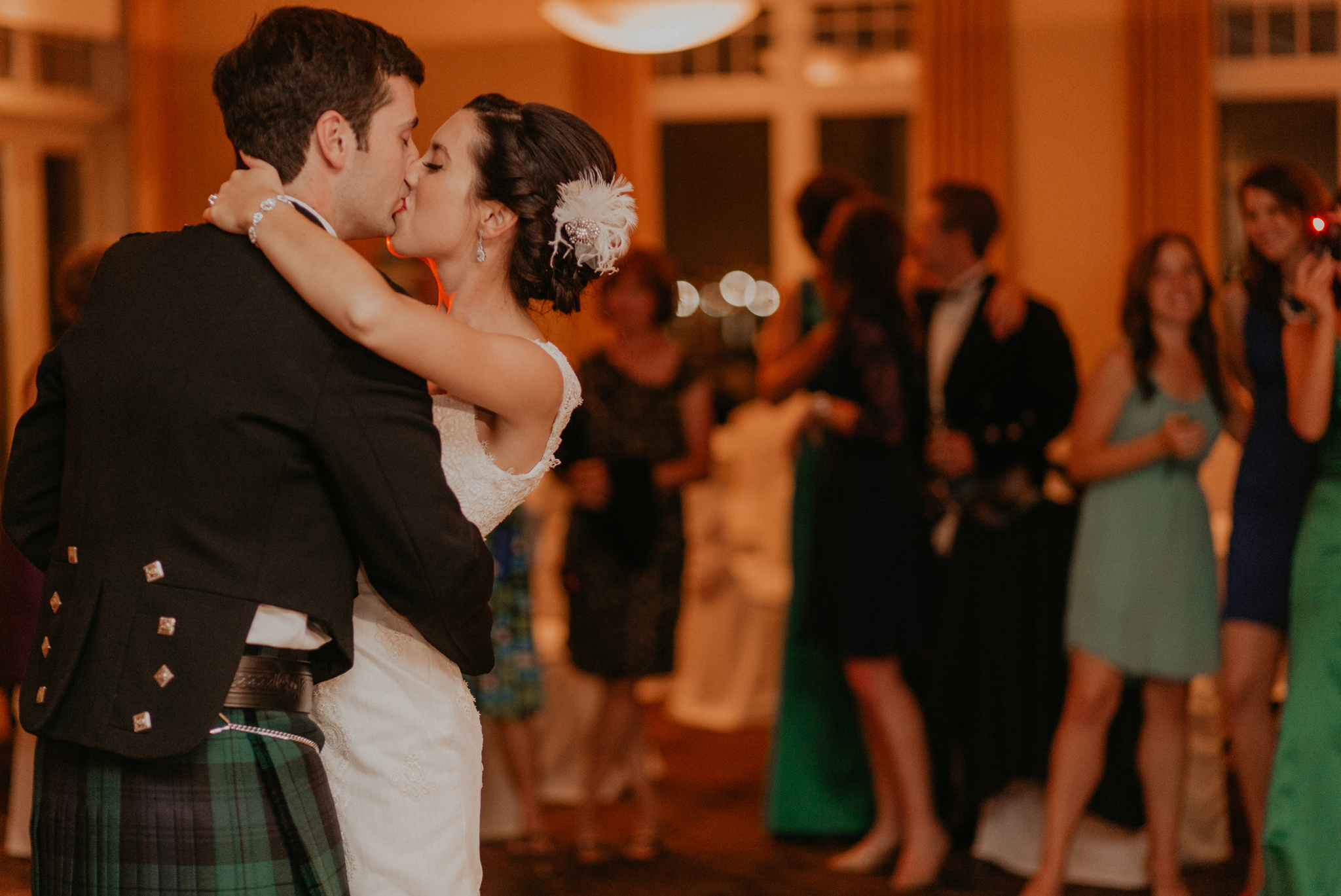 Candid photo of bride and groom kissing during first dance documentary wedding picture