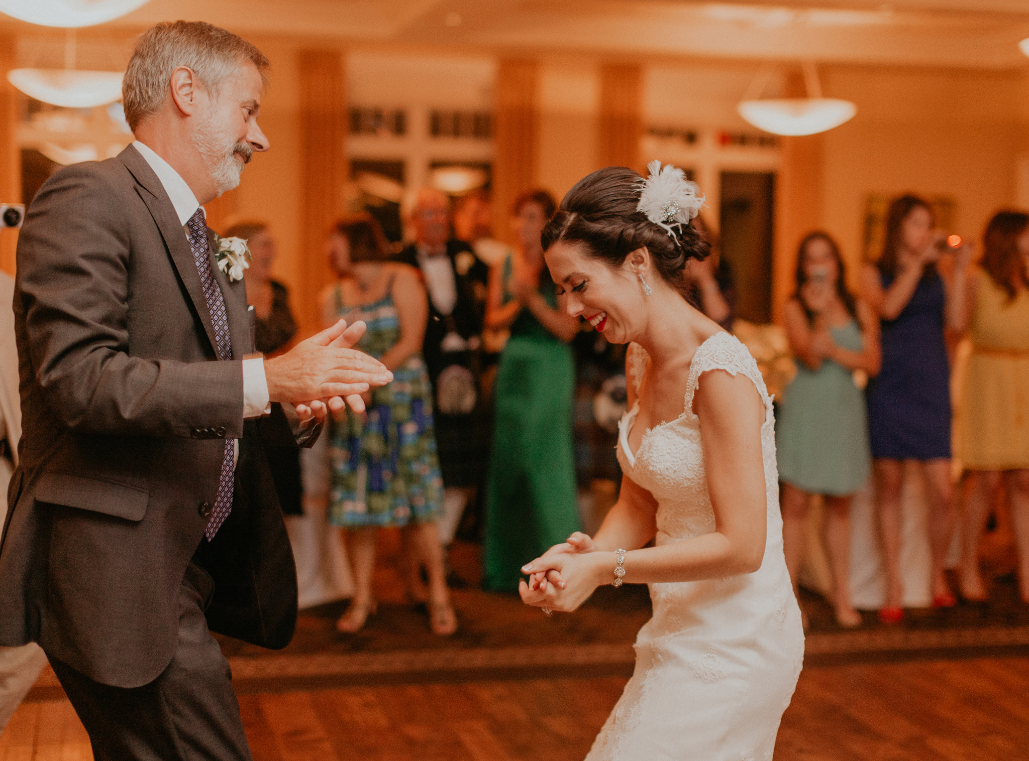 Bride smiles and has fun dancing with father during wedding