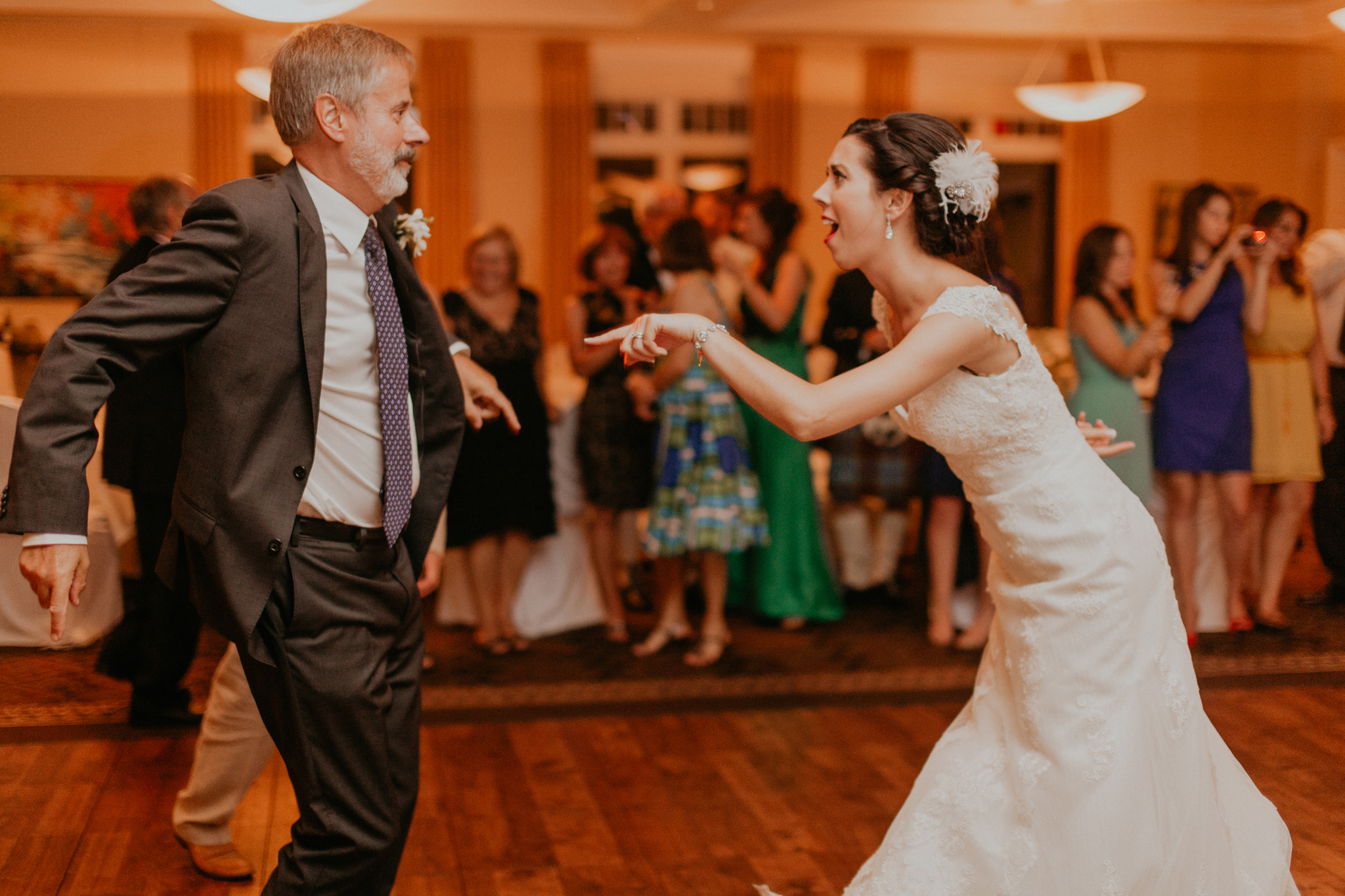 Bride smiles and has fun dancing with dad during wedding