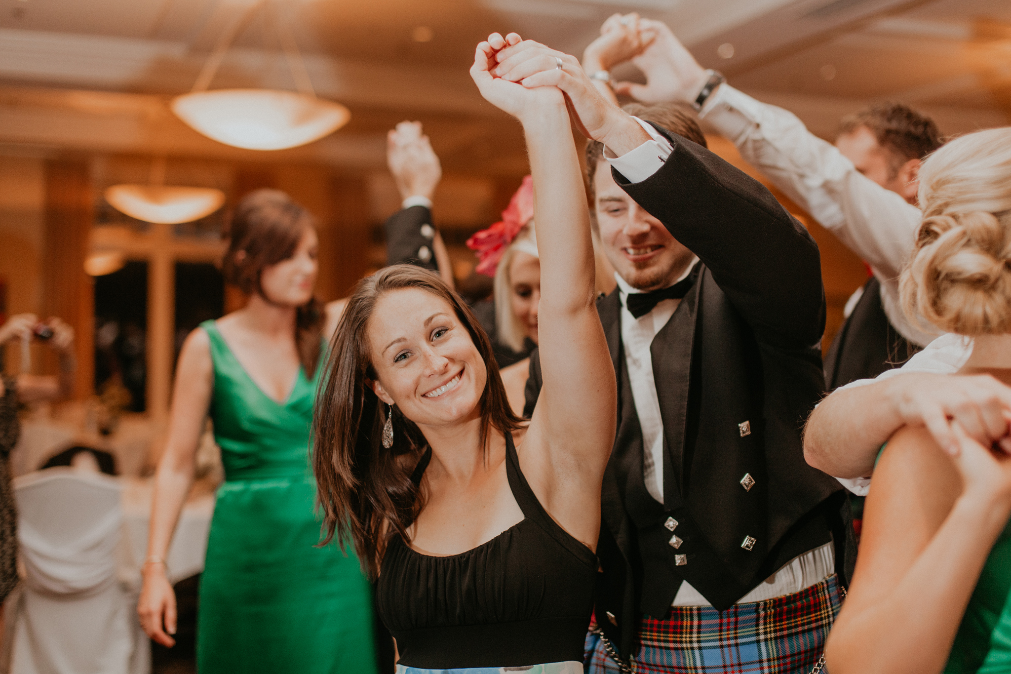 Guests smile and dance at wedding