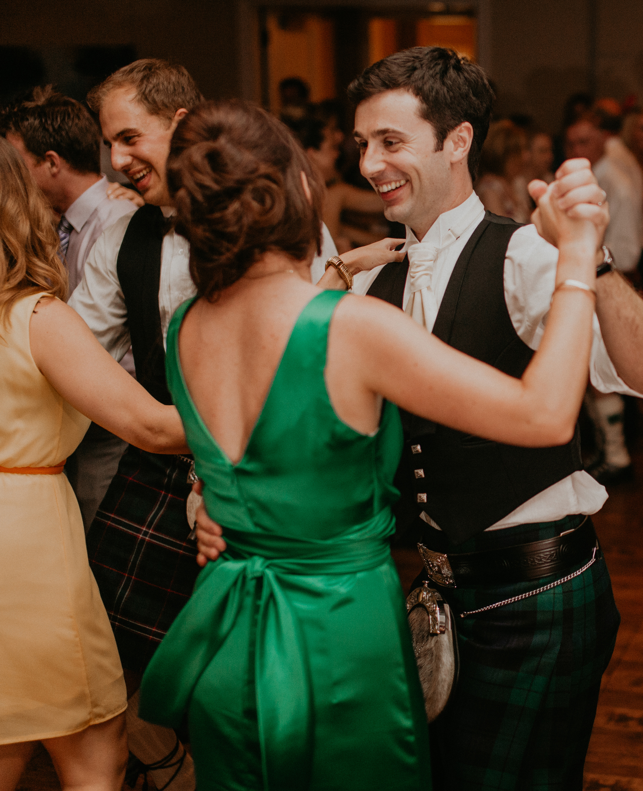 Groom dances with bridesmaid at wedding reception candid documentary photograph