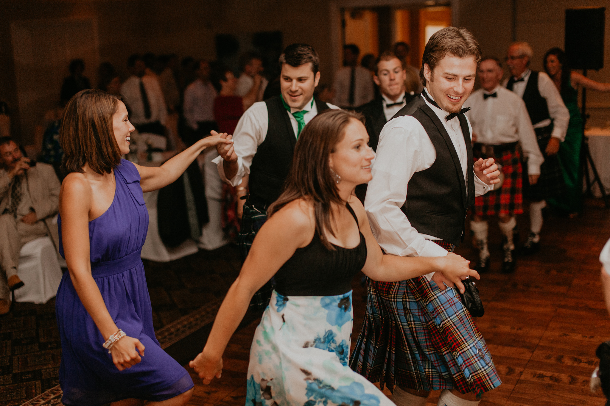 Guests dance in kilts at wedding reception candid documentary wedding photography