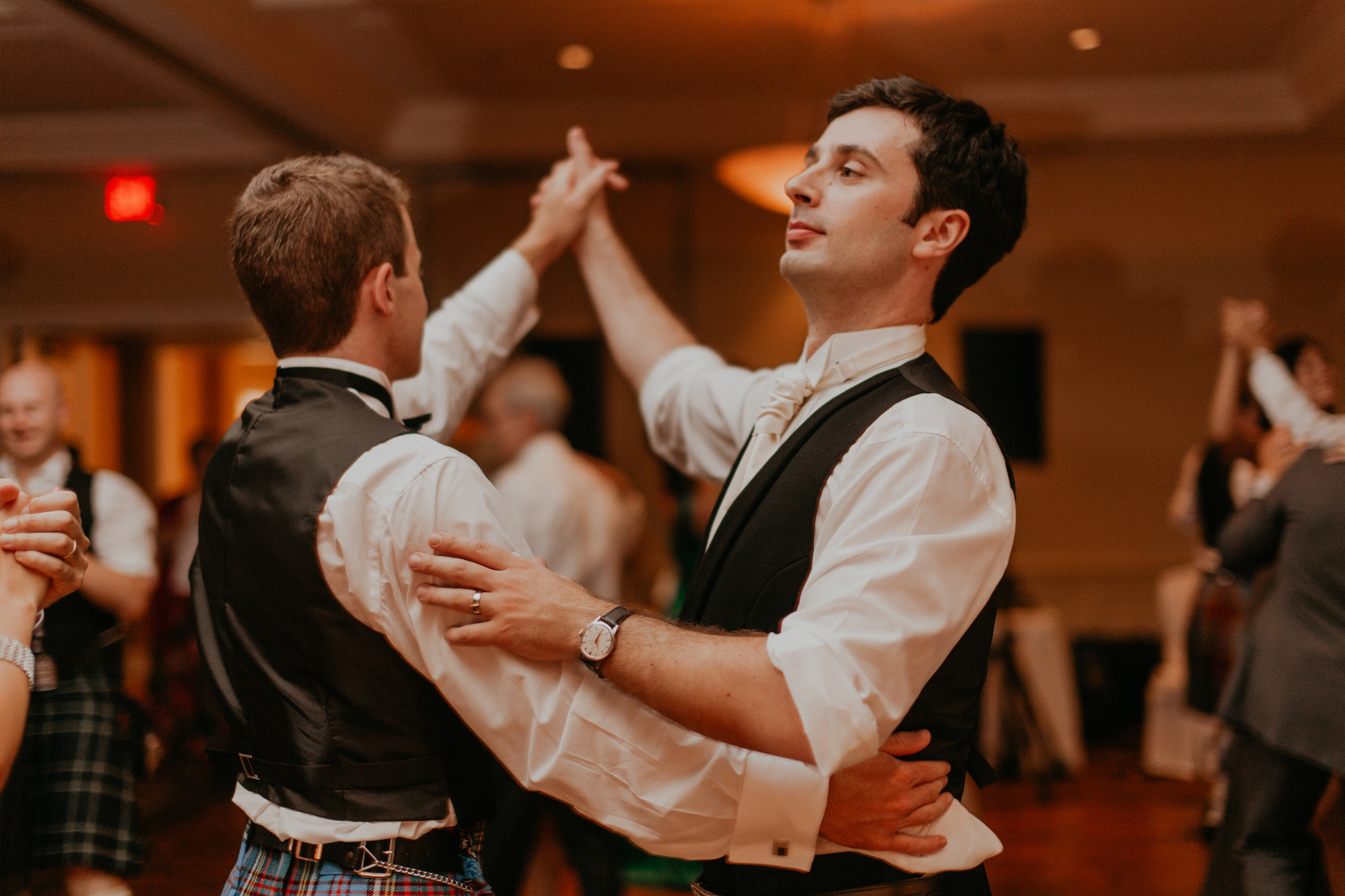 Groom and groomsmen dance in kilts at wedding reception candid documentary photography