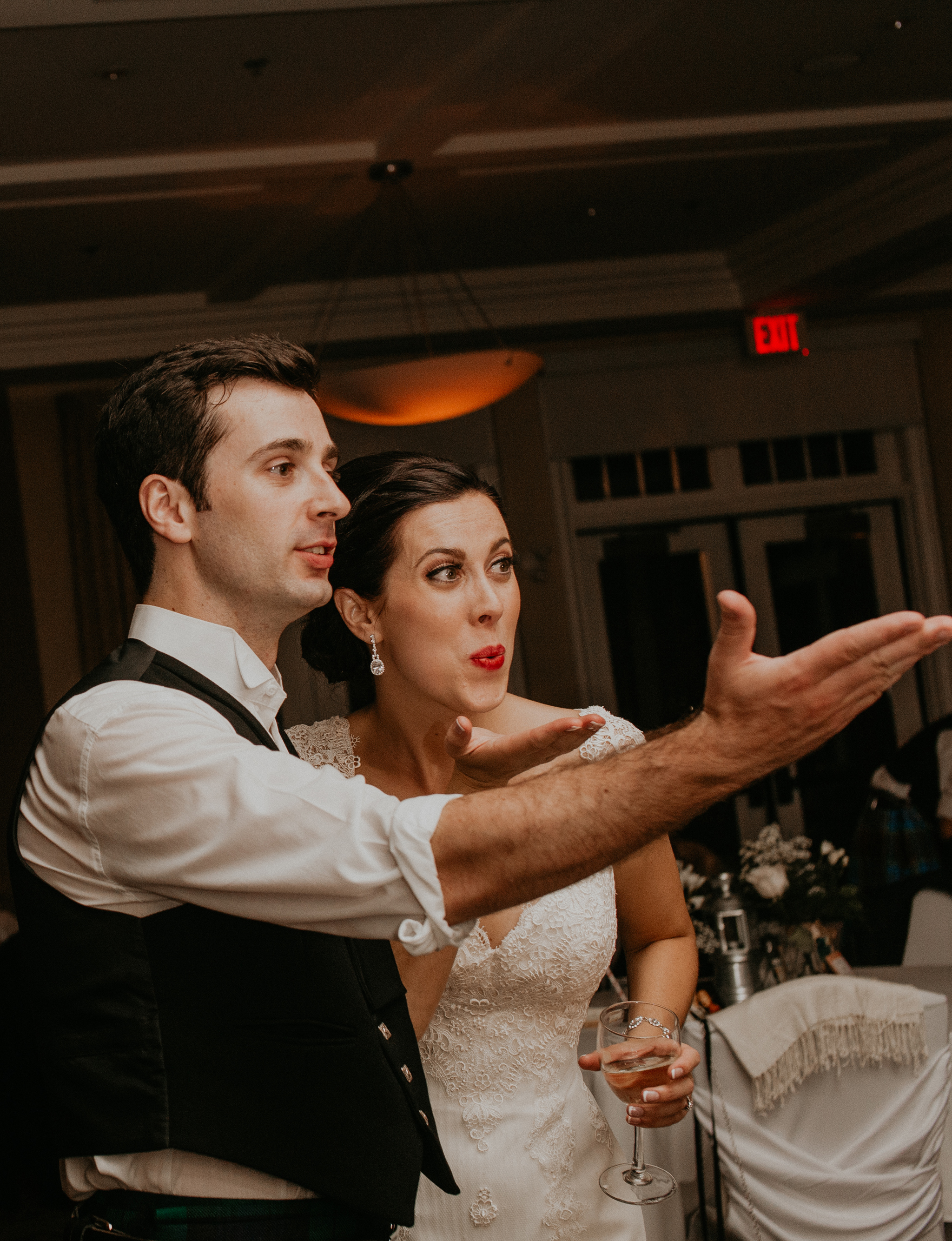 Candid moment of bride and groom blowing kiss at wedding reception