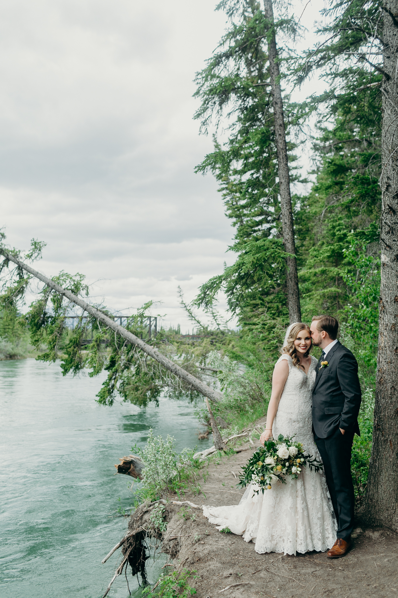 Bride and groom kiss in front of evergreens wedding portrait in Canmore AB