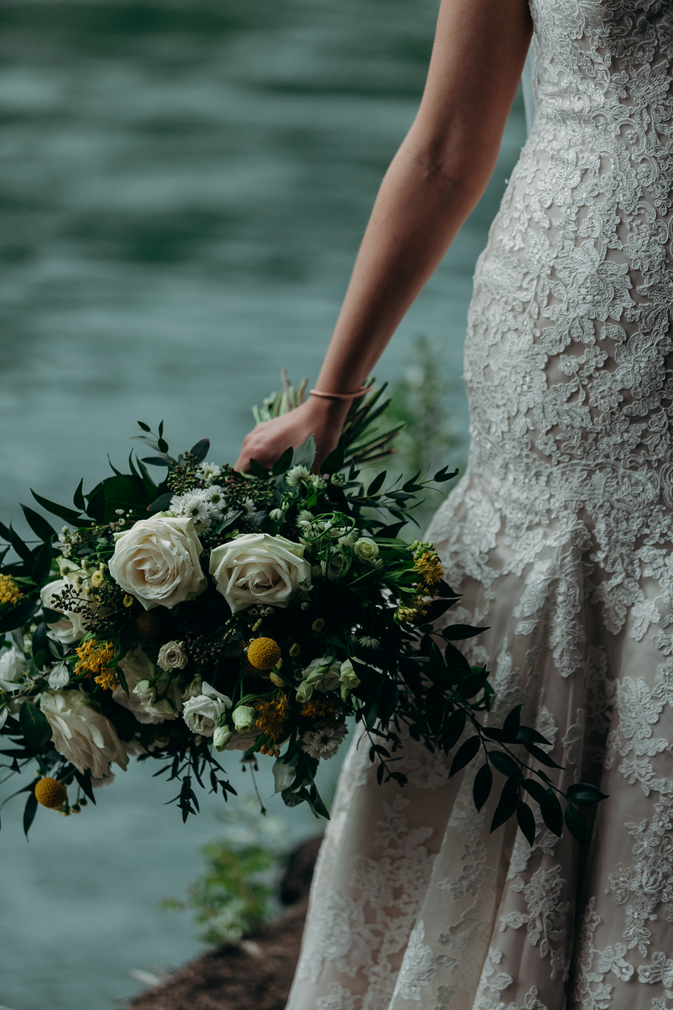 Close up of bride's bouquet and hand holding bouquet with Bow River in background