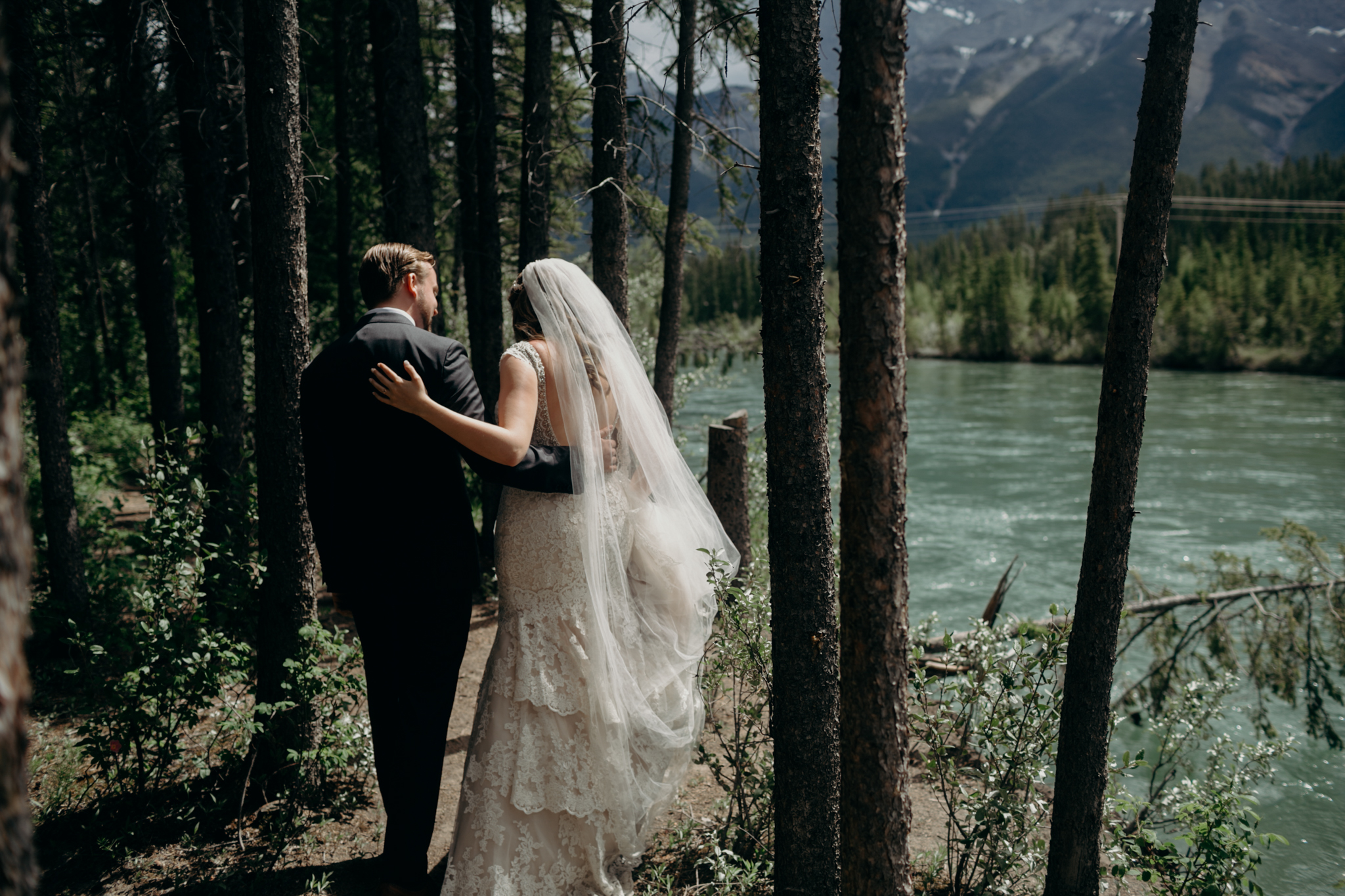 Bride and groom walk along Bow River romantic wedding photograph Banff AB