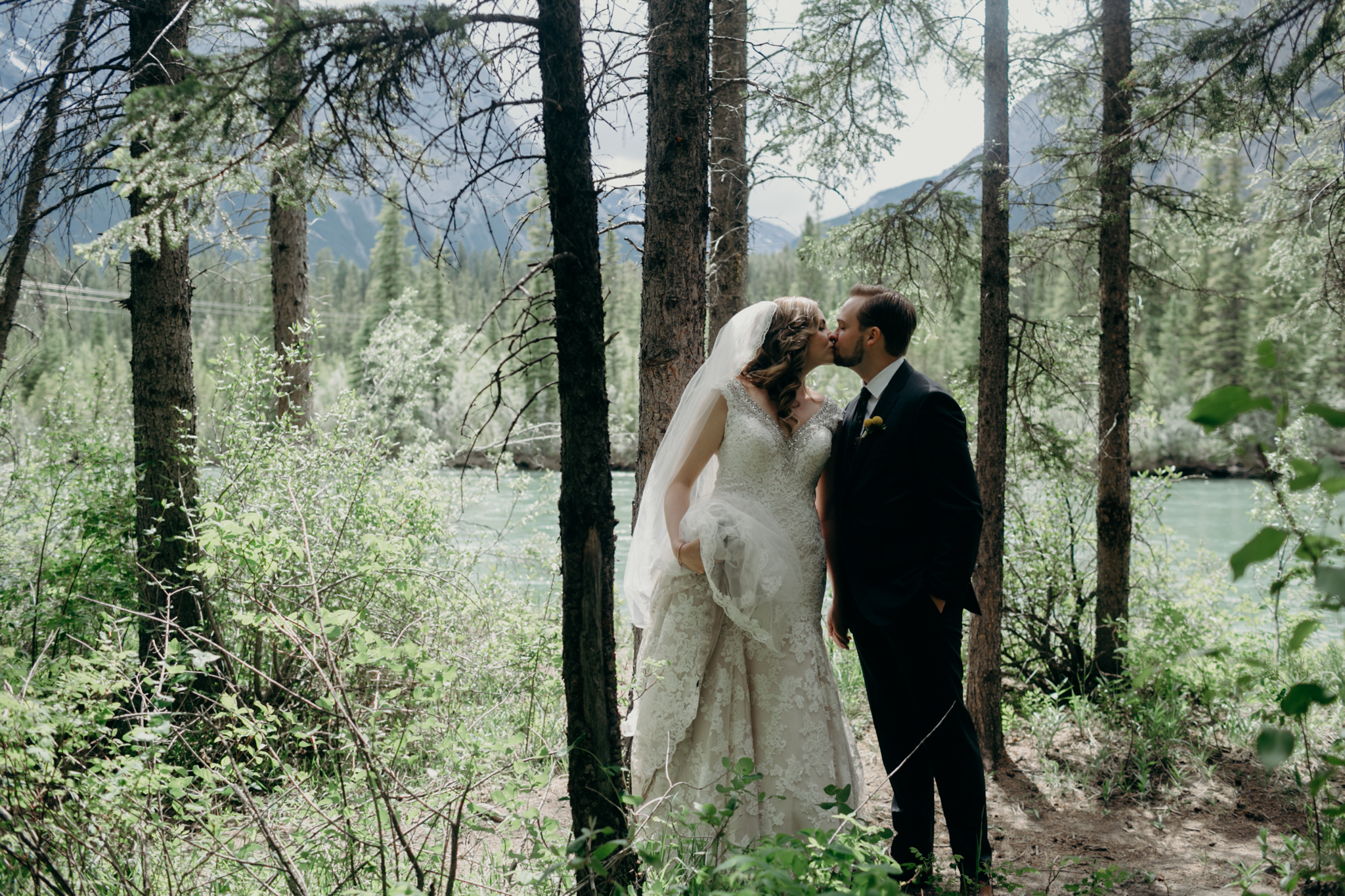 Bride and groom kiss with mountains and Bow River in background romantic Canmore photo