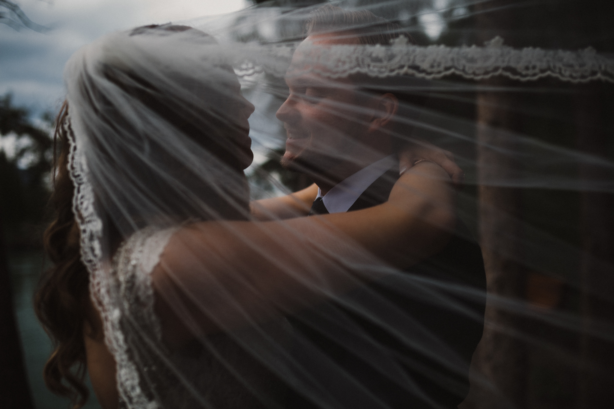 Bride and groom embrace underneath veil in moody portrait