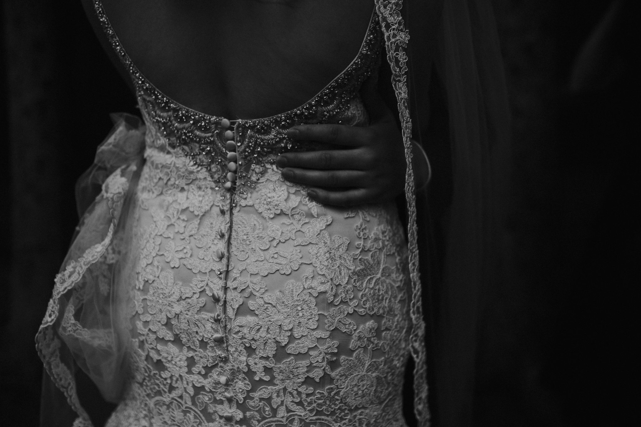 Black and white photo of groom's hand on bride's back moody photo