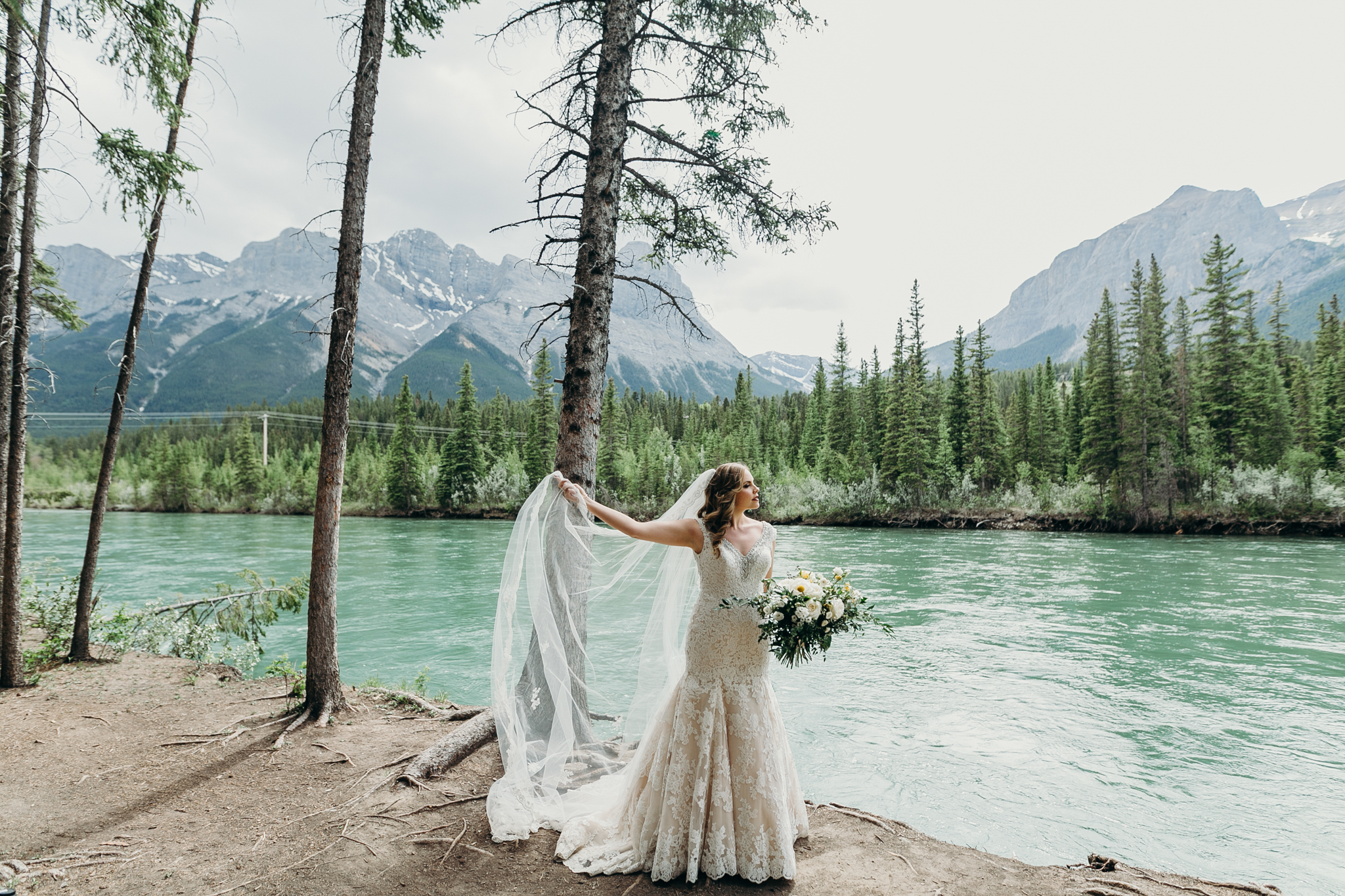 Bride plays with veil on edge of Bow River Canmore AB