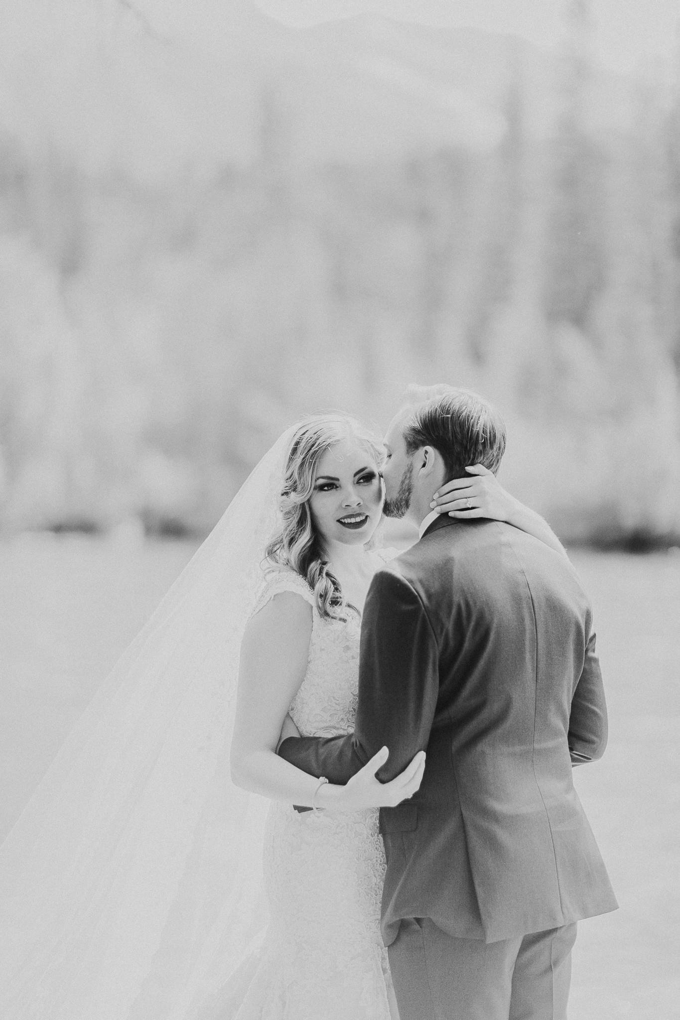 Black and white photo of groom kissing bride's cheek in Canmore AB