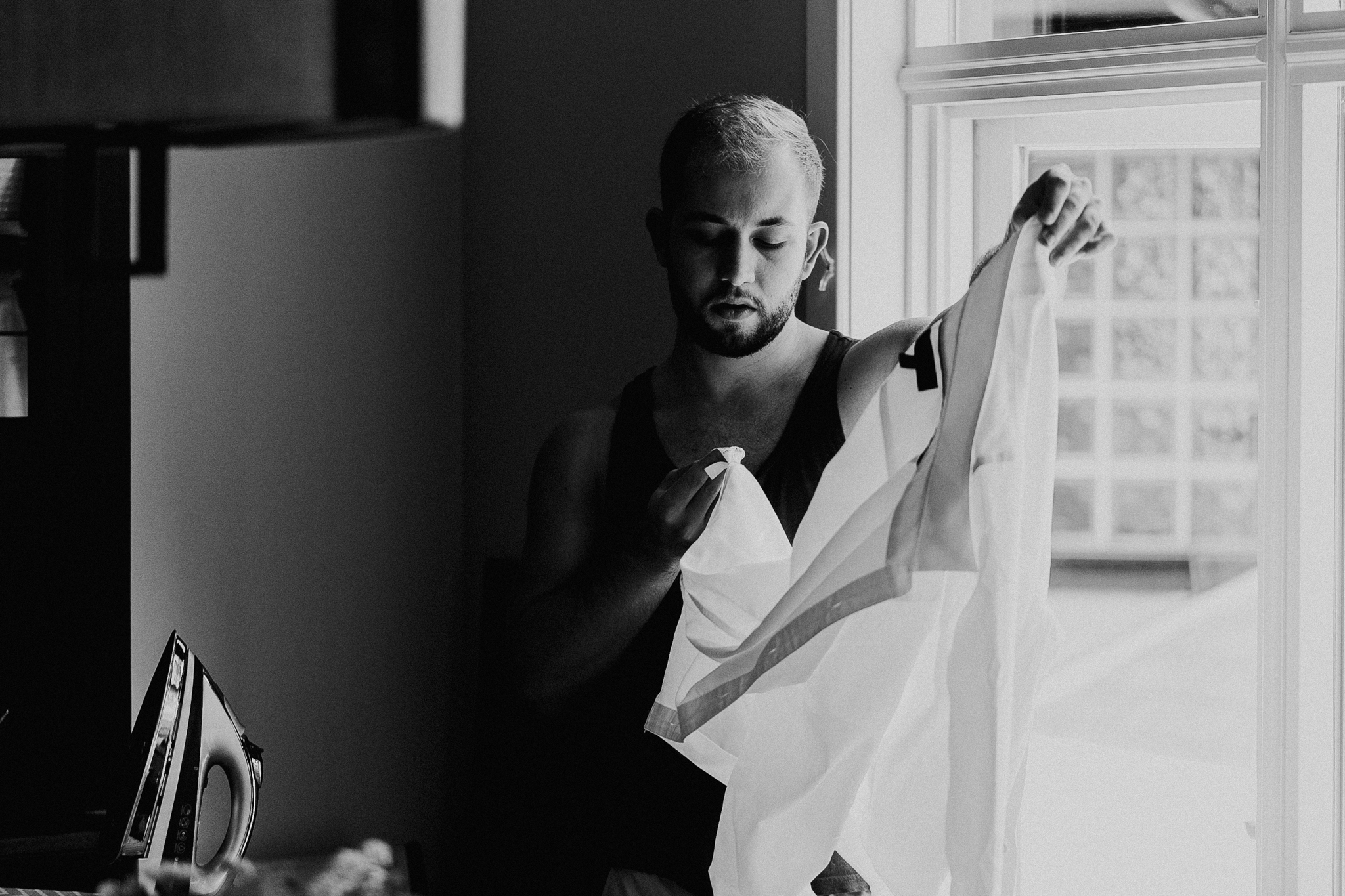 Groomsman ironing dress shirt for wedding candid photo