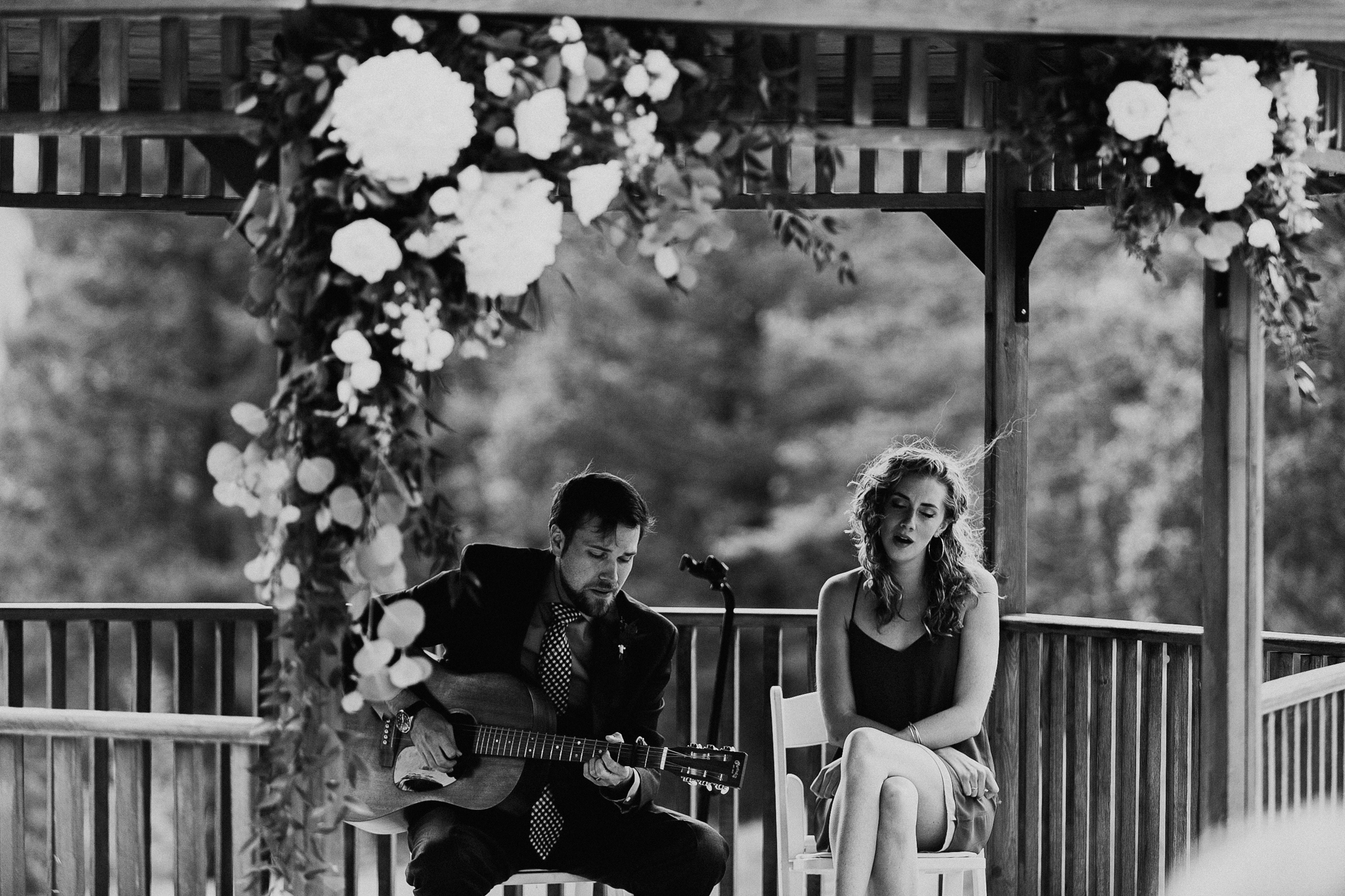 Man plays guitar and woman sings in Silvertip Resort Gazebo Canmore Alberta