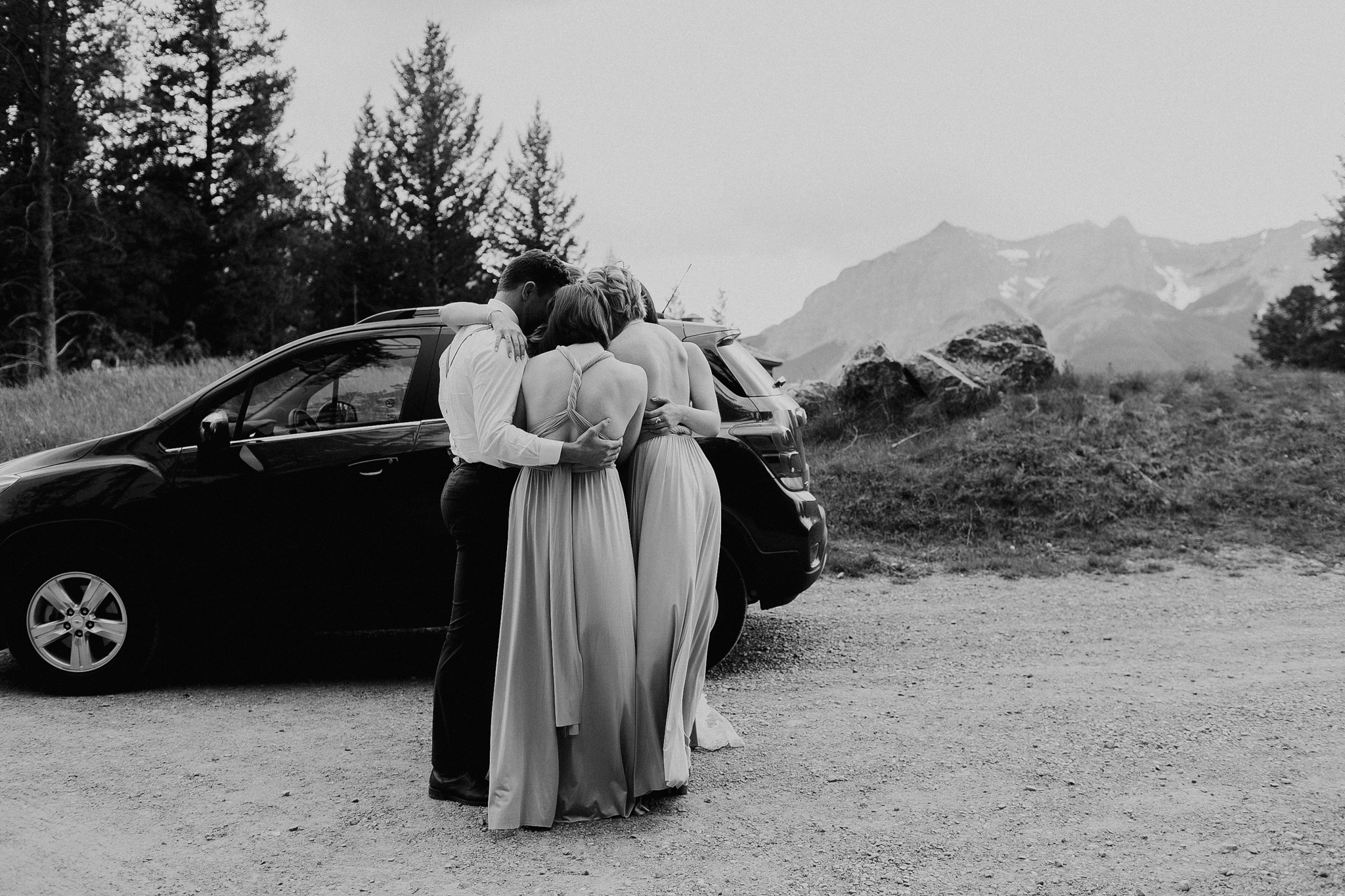 Wedding party wraps arms and prays at wedding ceremony Silvertip Resort Canmore AB