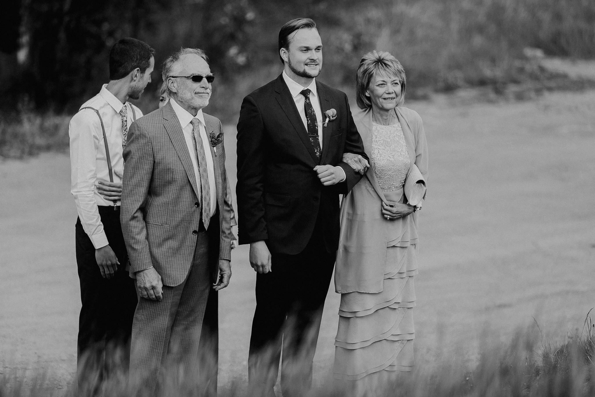 Black and white photo of groom walking aisle with mom and dad Silvertip Resort Canmore AB