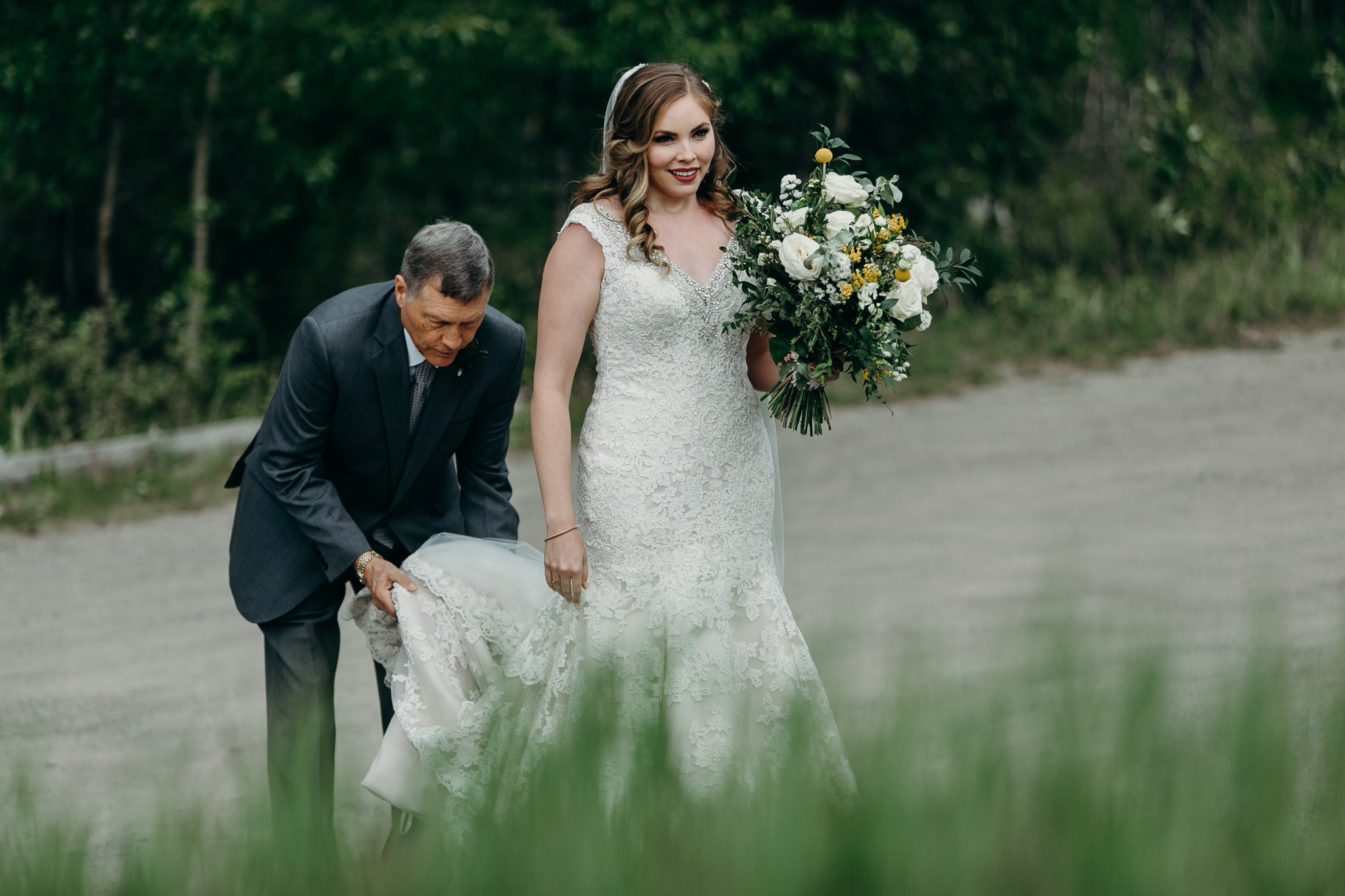 Father fixes brides dress at Silvertip Resort Canmore Alberta wedding ceremony