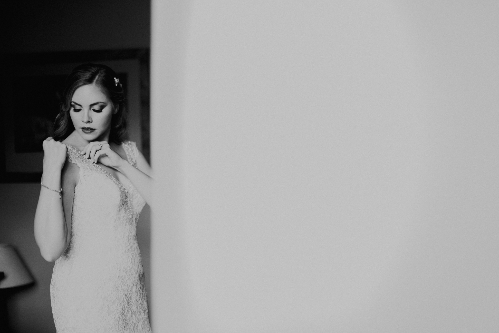 Bride putting on wedding dress black and white photo