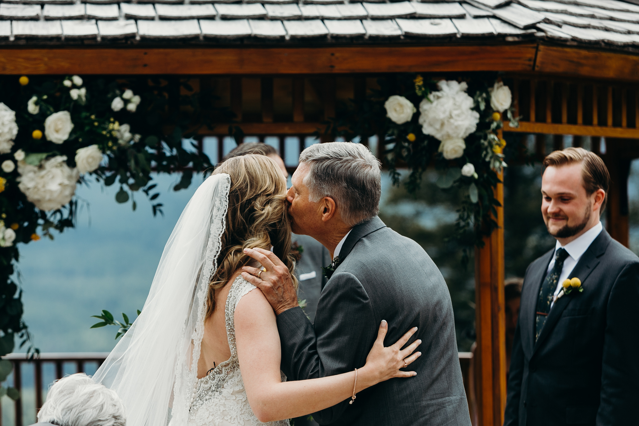 Father kisses Bride's cheek at Silvertip Resort's gazebo wedding ceremony Canmore AB