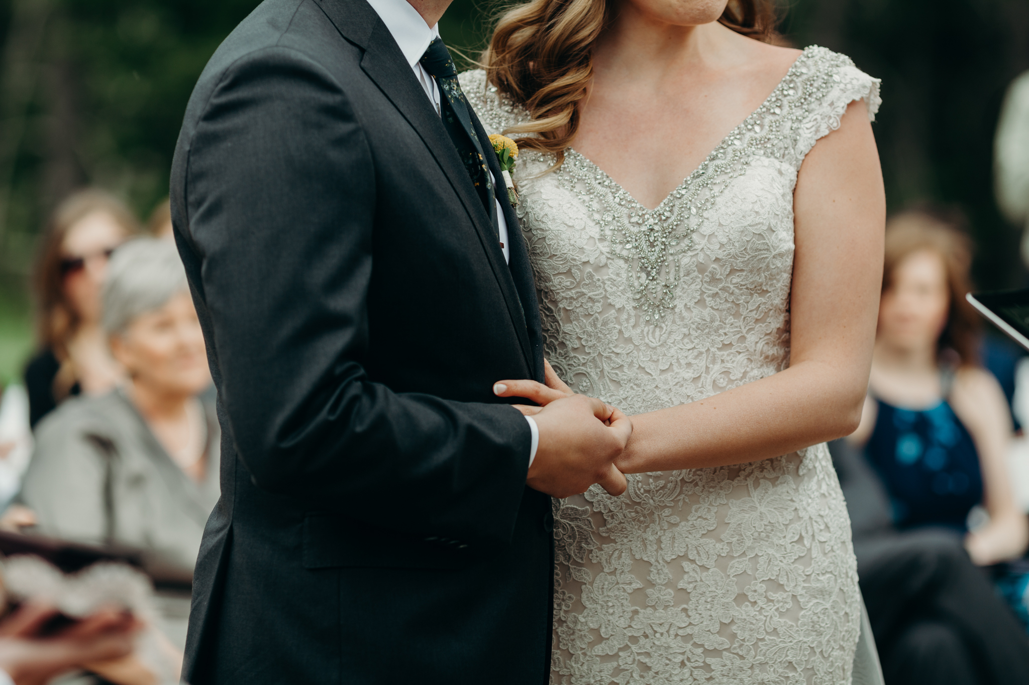 Close up photo of bride and groom holding hands at wedding ceremony