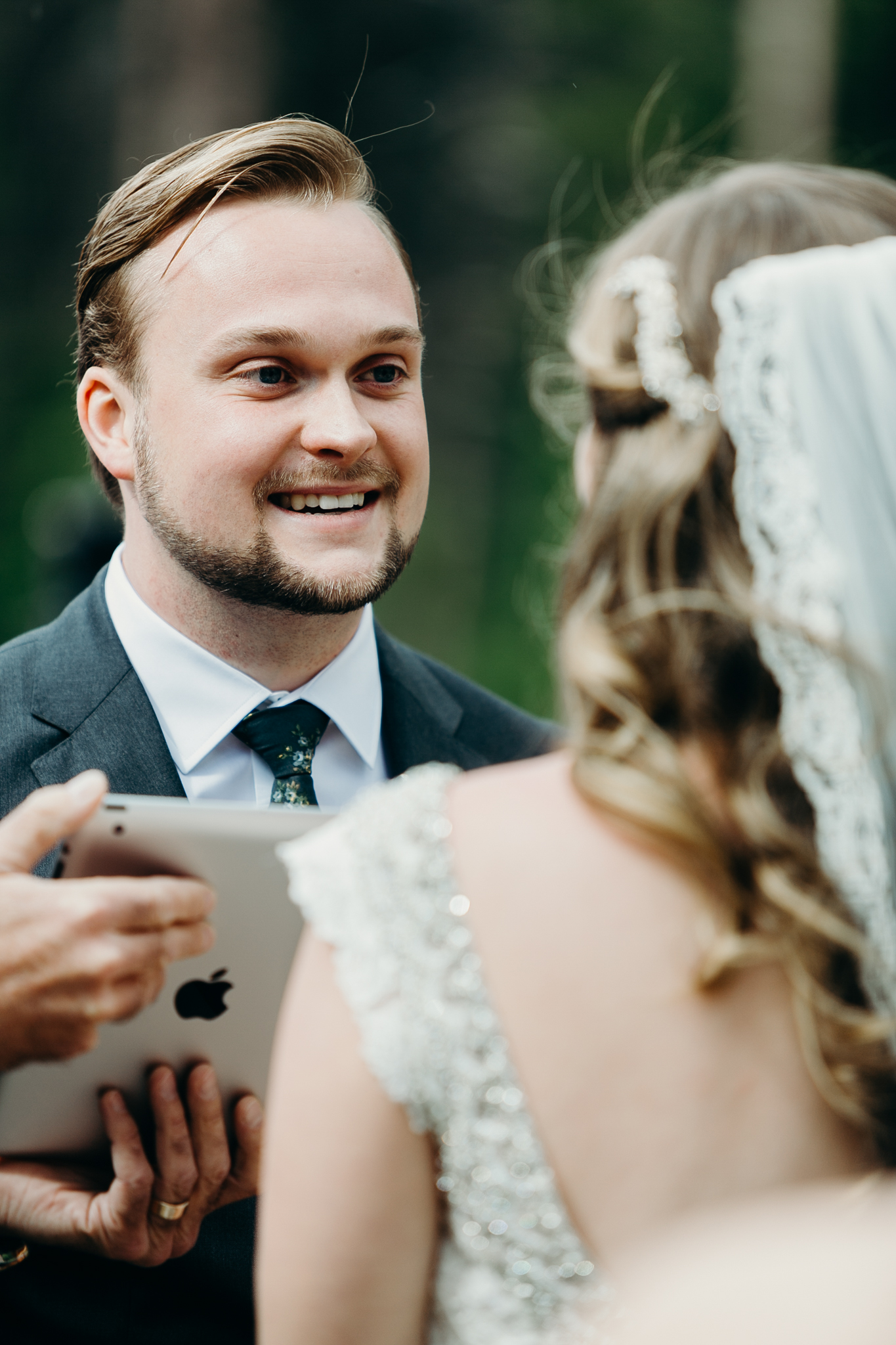 Groom smiles at bride during Silvertip Resort wedding ceremony in Canmore Alberta