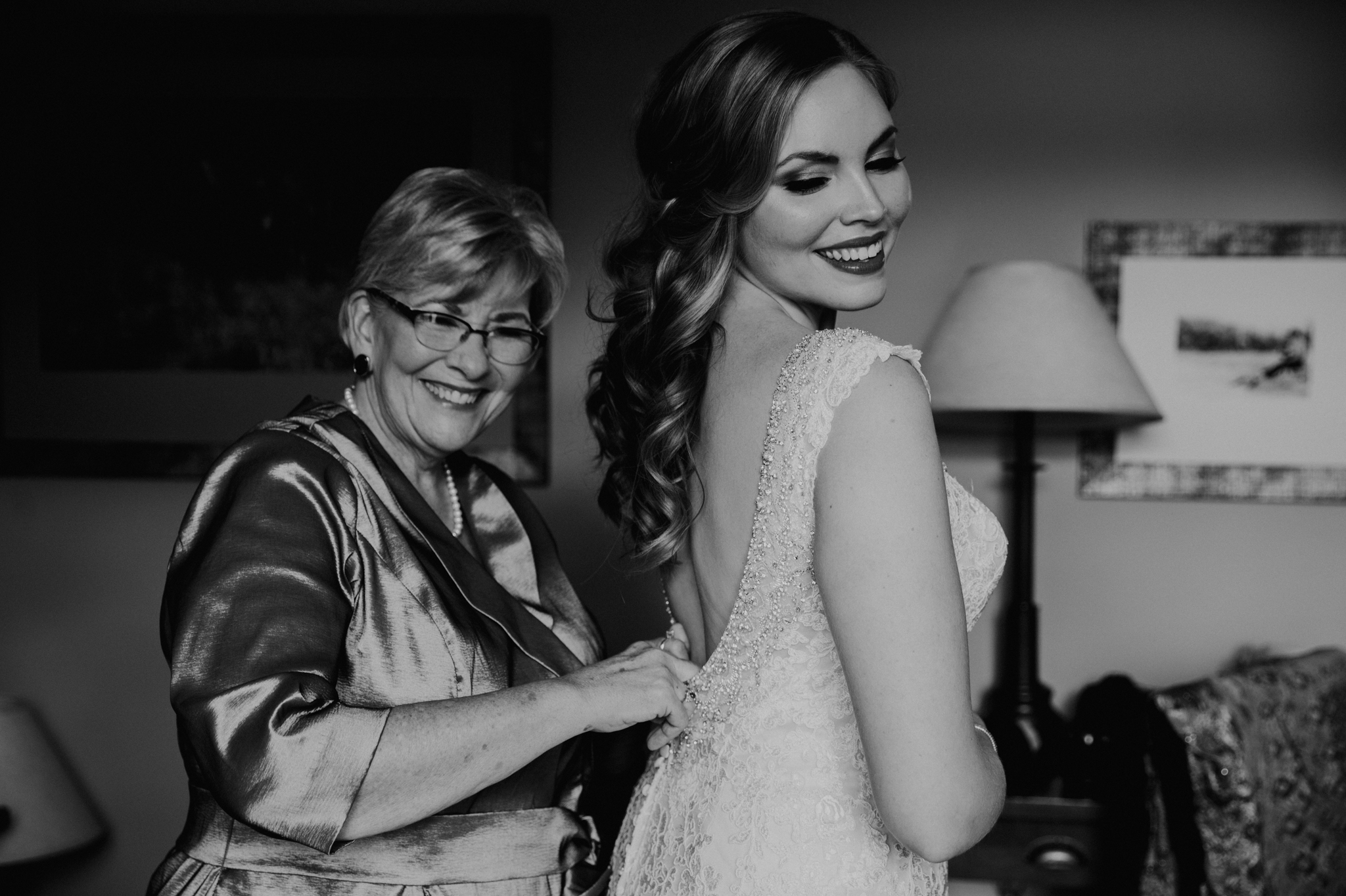 Mother of the bride helping bride put on wedding dress documentary wedding photographer MN
