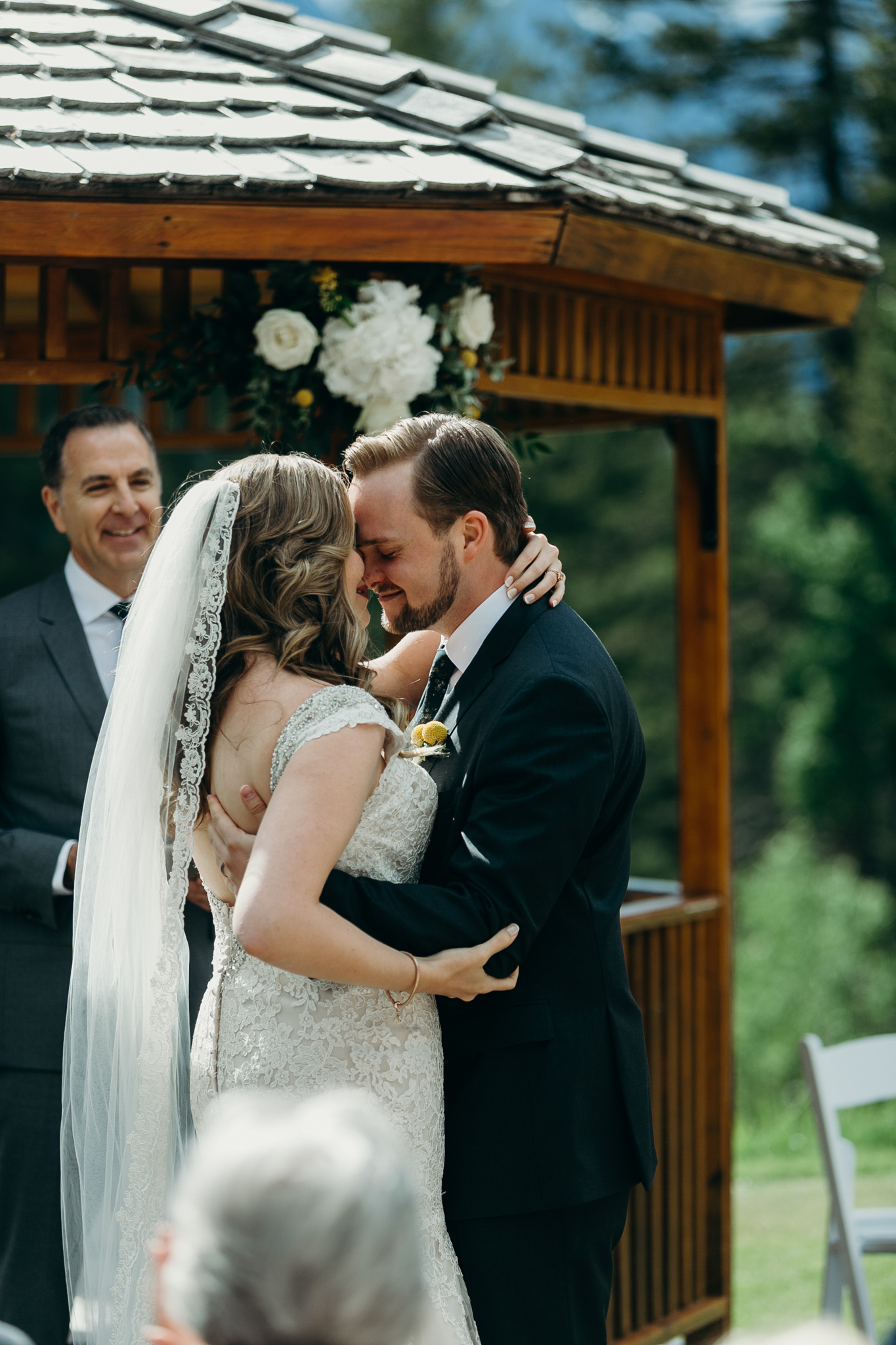 Bride and groom kiss at Silvertip Resort in front of gazebo and mountains