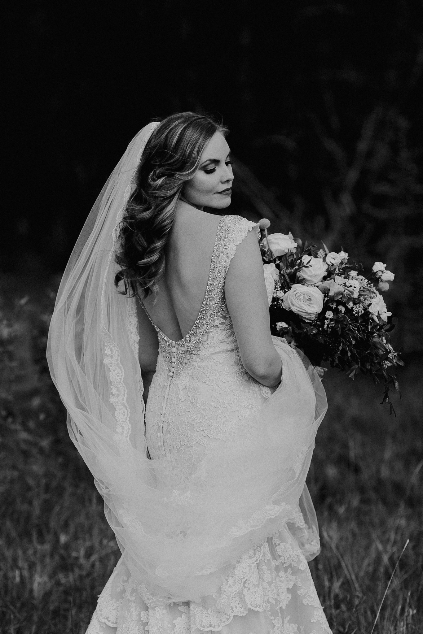 Bride poses for photo in black and white portrait at Silvertip Resort Canmore destination wedding